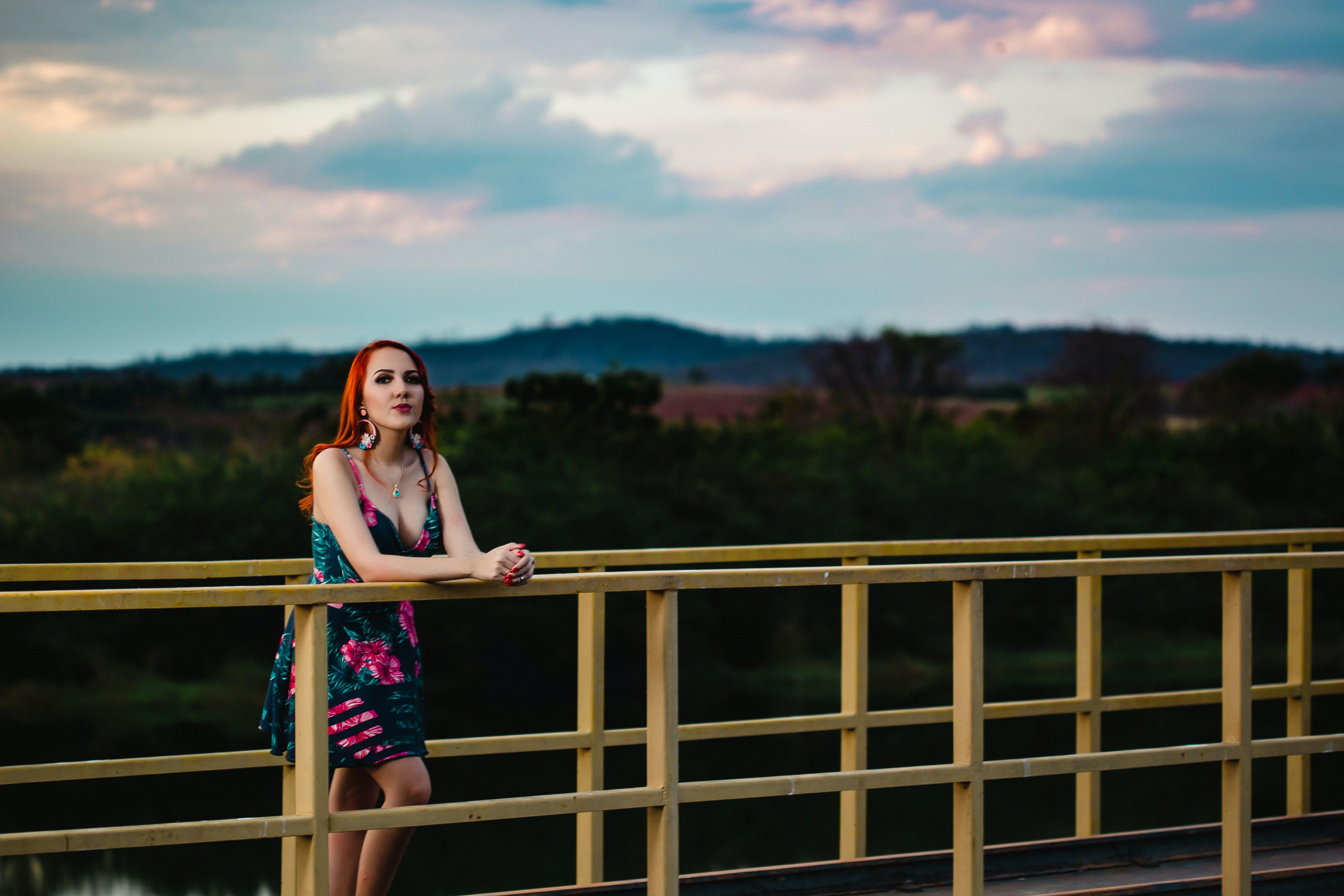 Woman Leaning on Yellow Steel Fence on Bridge
