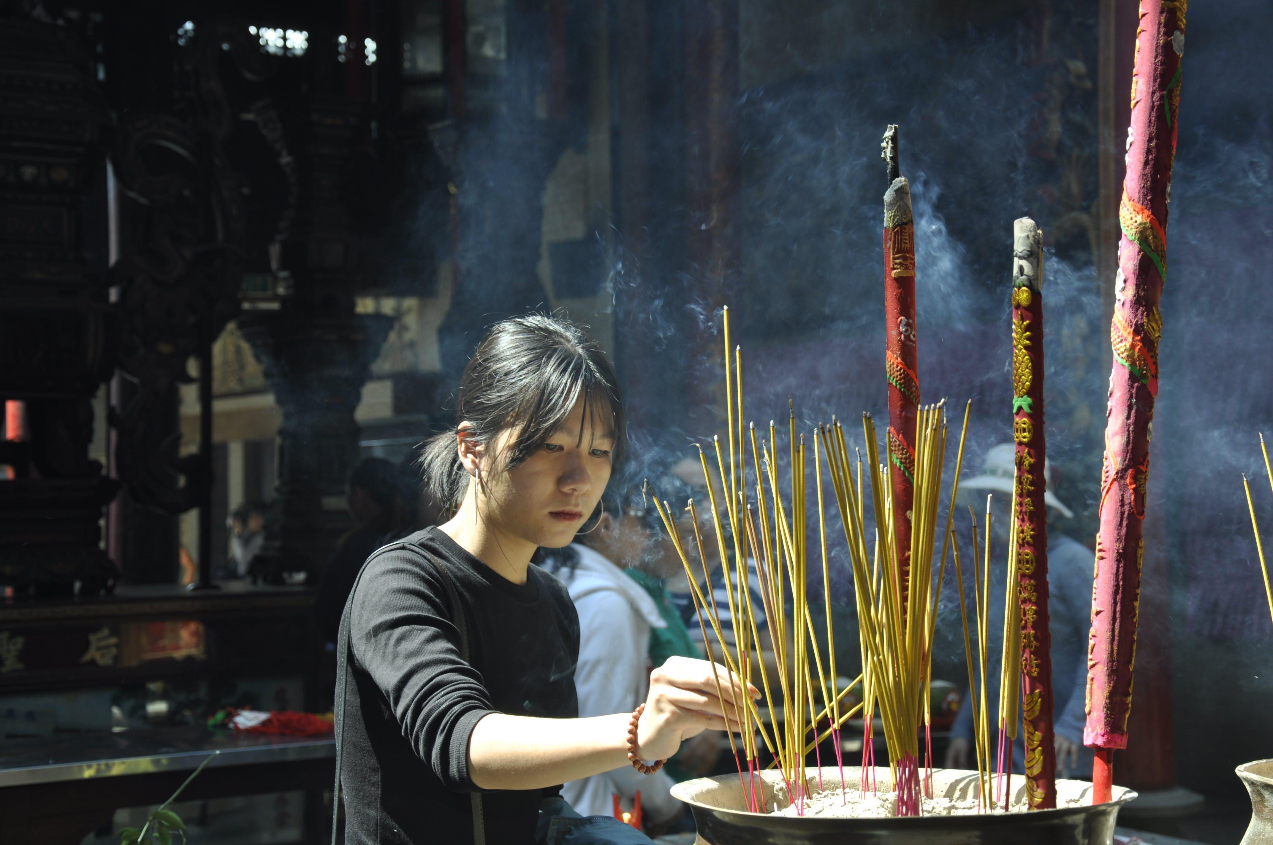 Woman Lighting Incense Sticks
