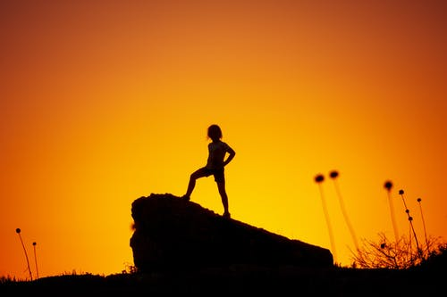 Silhouette Photography of Kid Standing on Rock