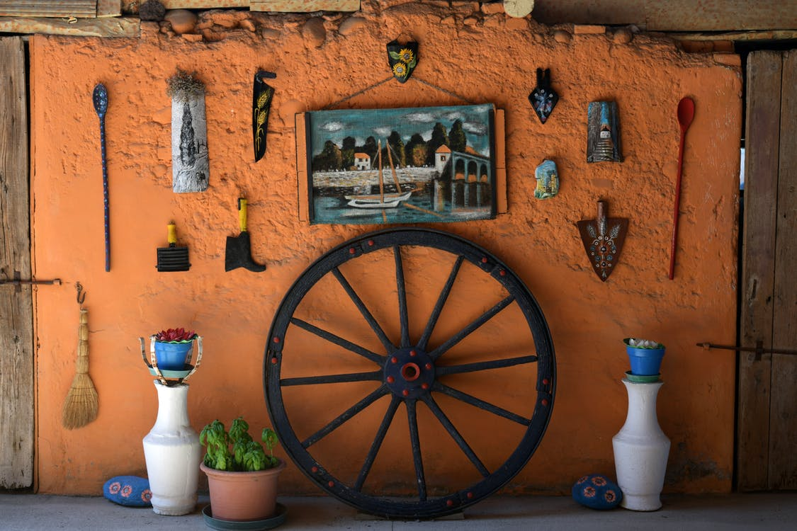 Black Wooden Carriage Wheel Leaning on Orange Painted Wall