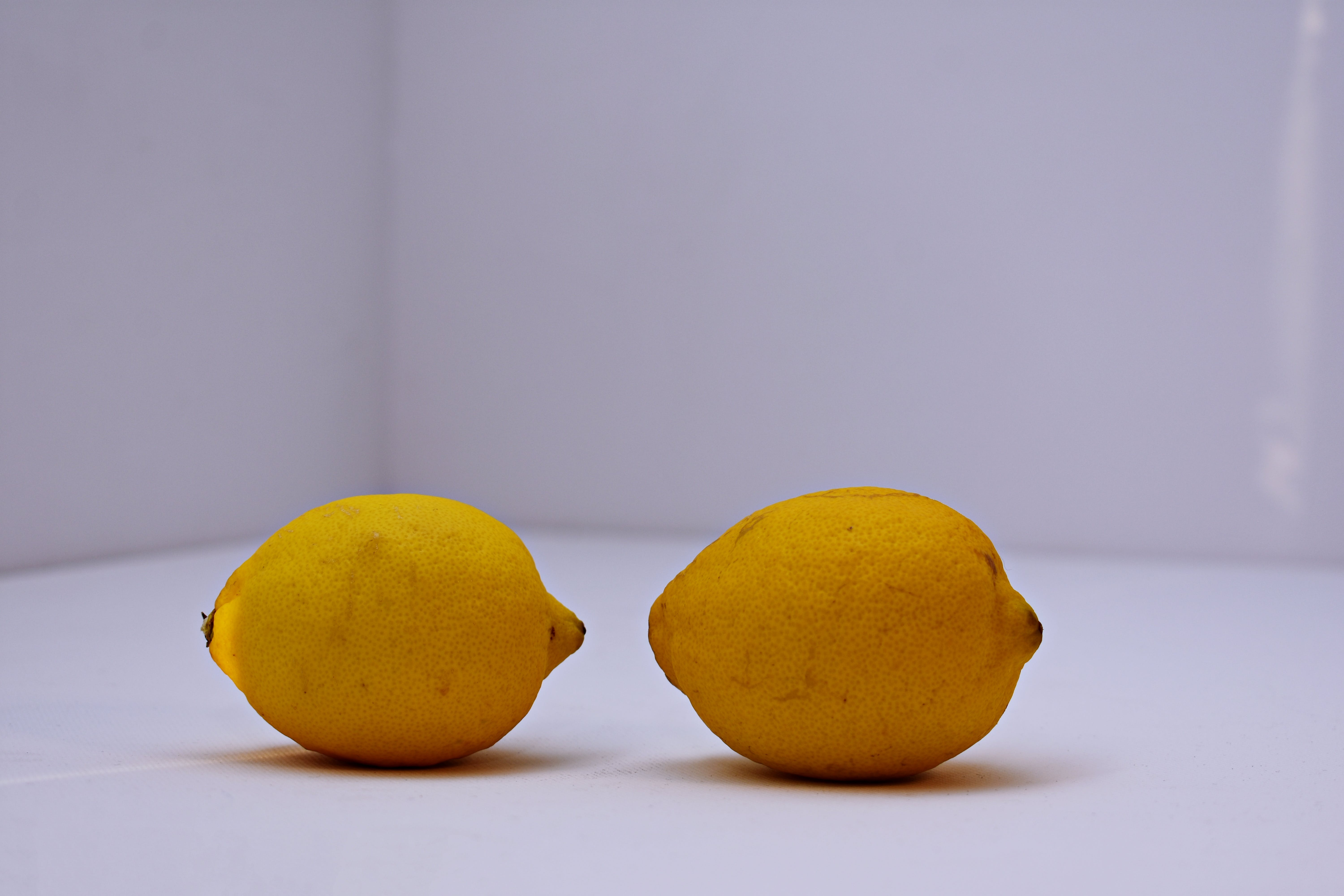 Two Yellow Lemons on White Surface