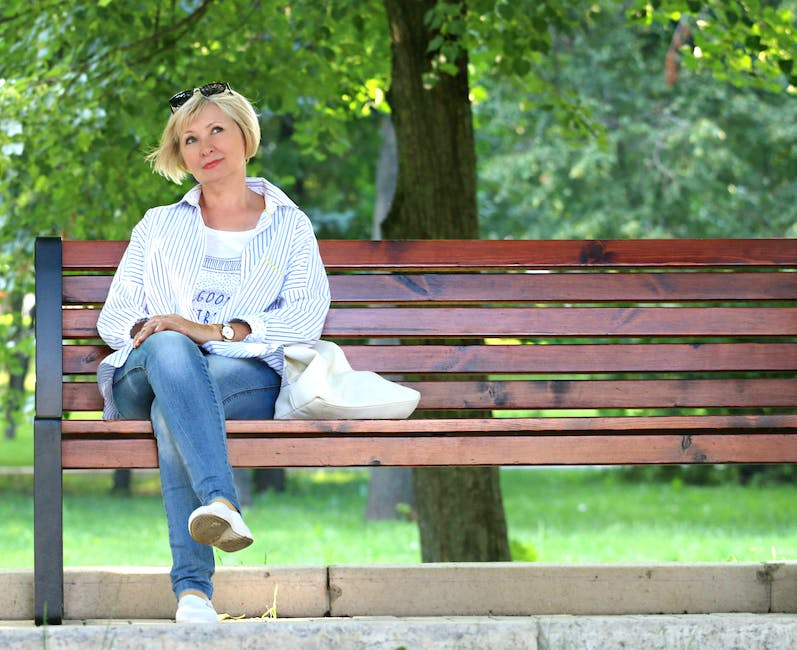 Thinking Woman in White Jacket and White Scoop Neck Shirt Blue Denim Jeans Sitting on Brown Wooden Bench Beside Green Trees during Daytime