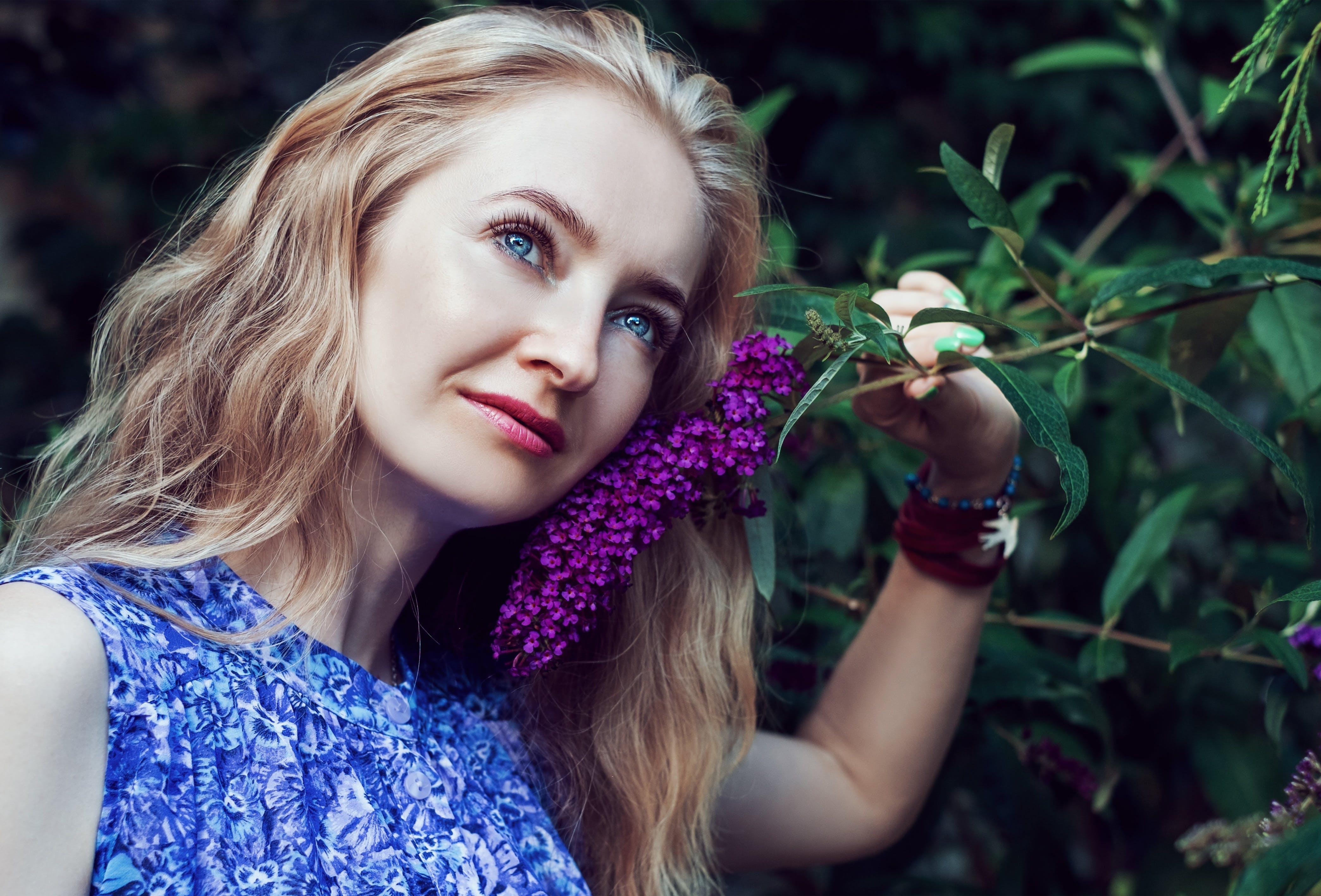 Woman Wearing Blue Floral Sleeveless Dress Smelling Violet Flower