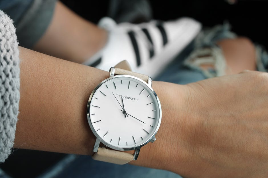 Beige Strap Silver Round Analog Watch Behind Adidas White and Black Superstar