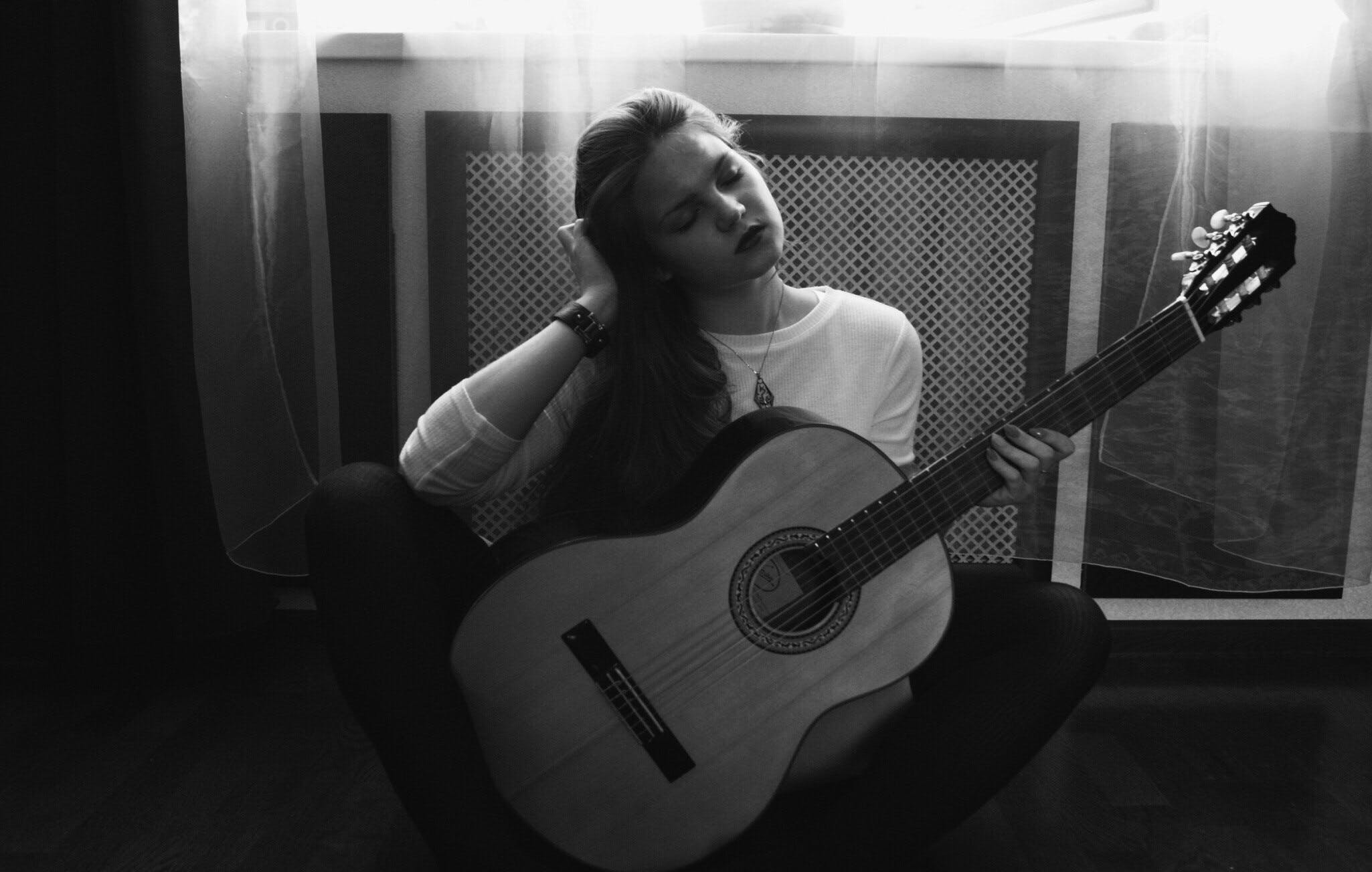 Greyscale Photography of Woman in Crew Neck Long Sleeve Shirt Holding Guitar