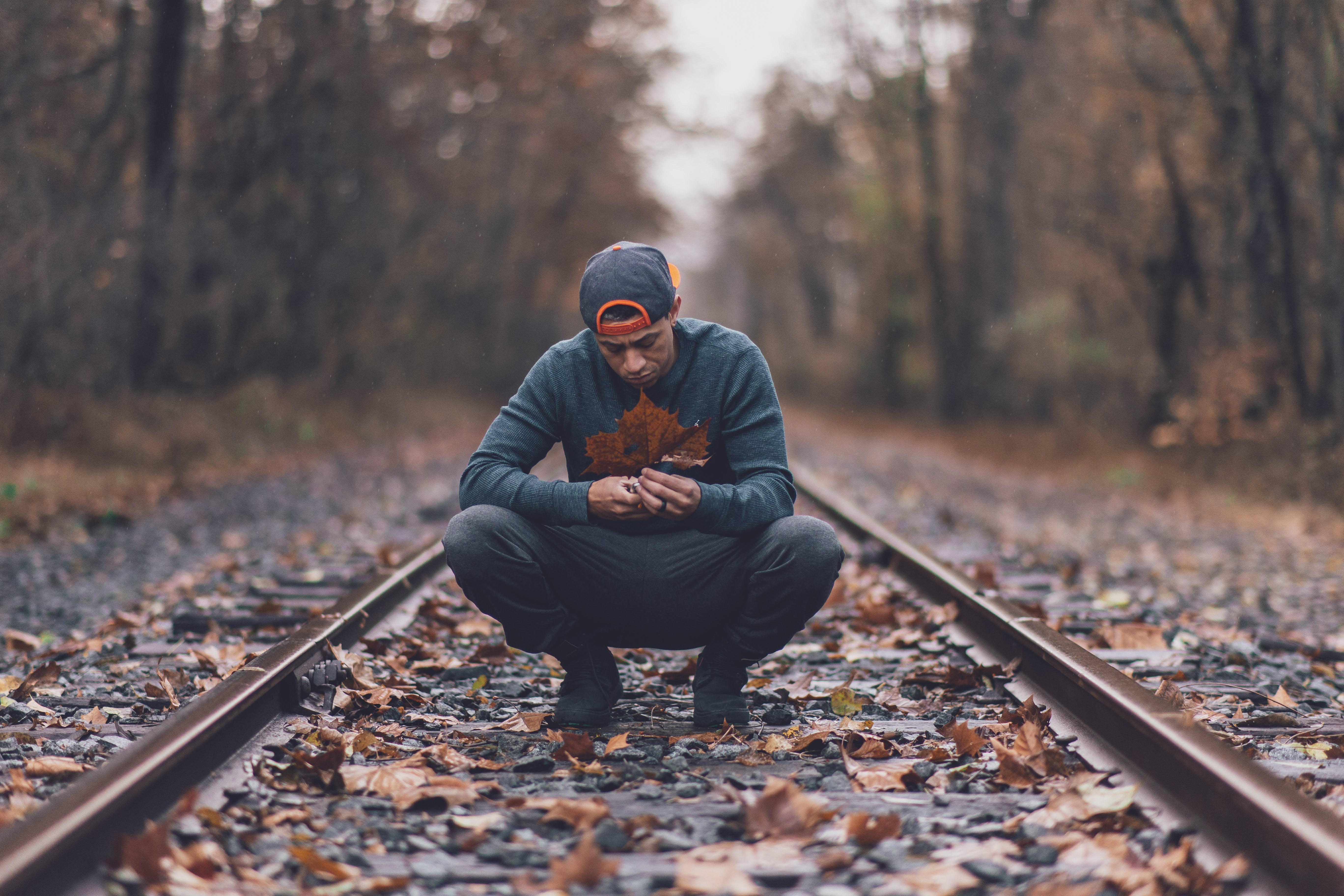 Man Squatting on Railroad
