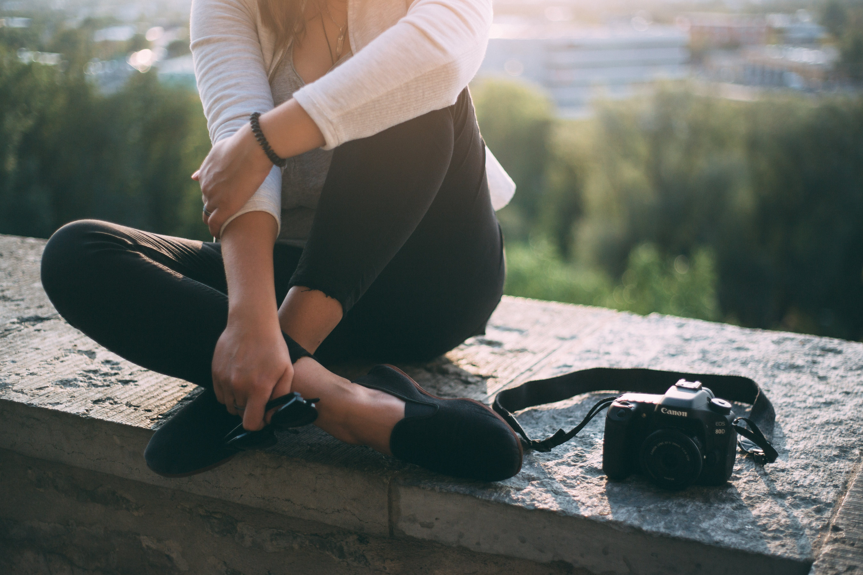 Woman Sitting Beside Black Canon Dslr Camera