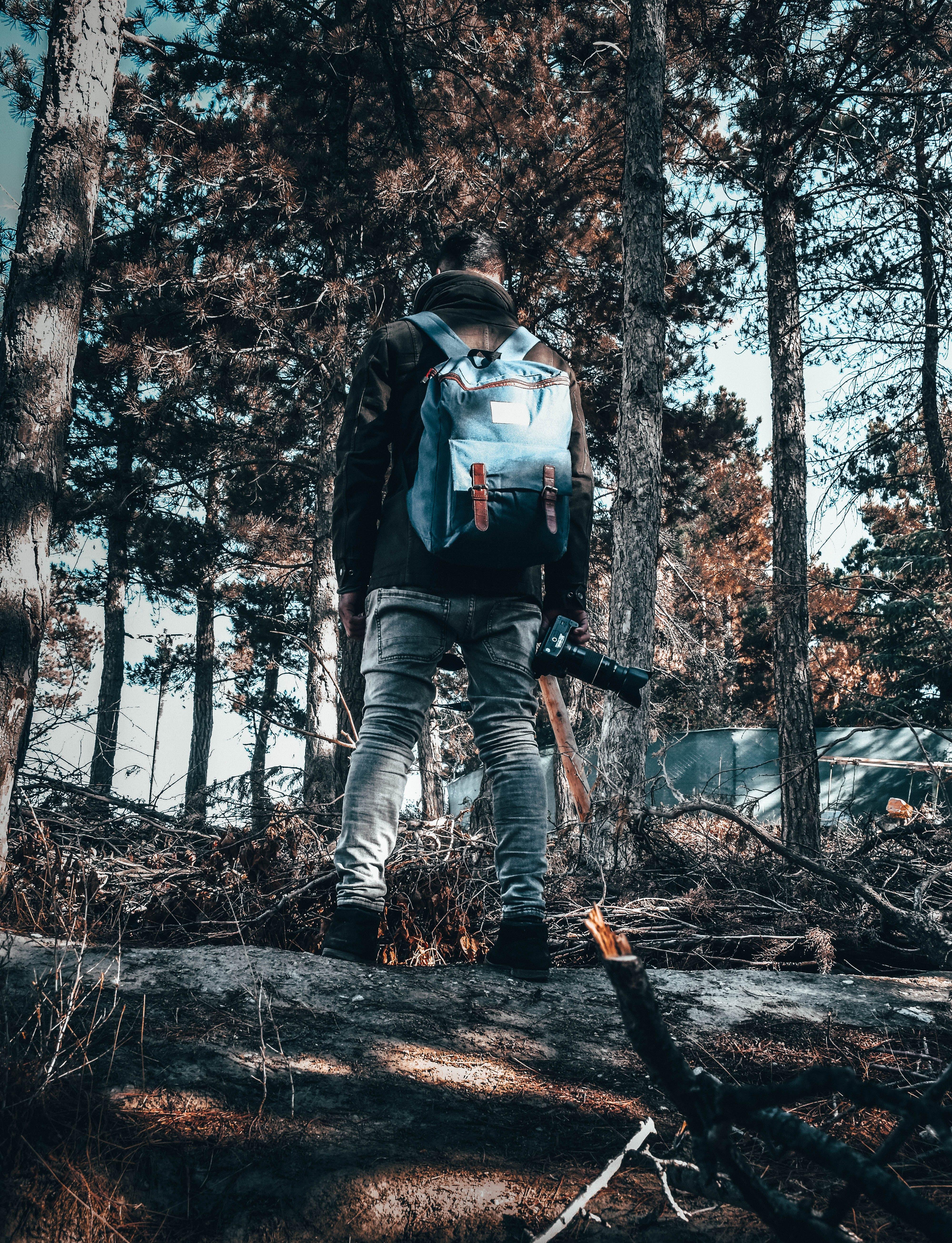 Man Wearing Gray Pants Standing Beside Trees
