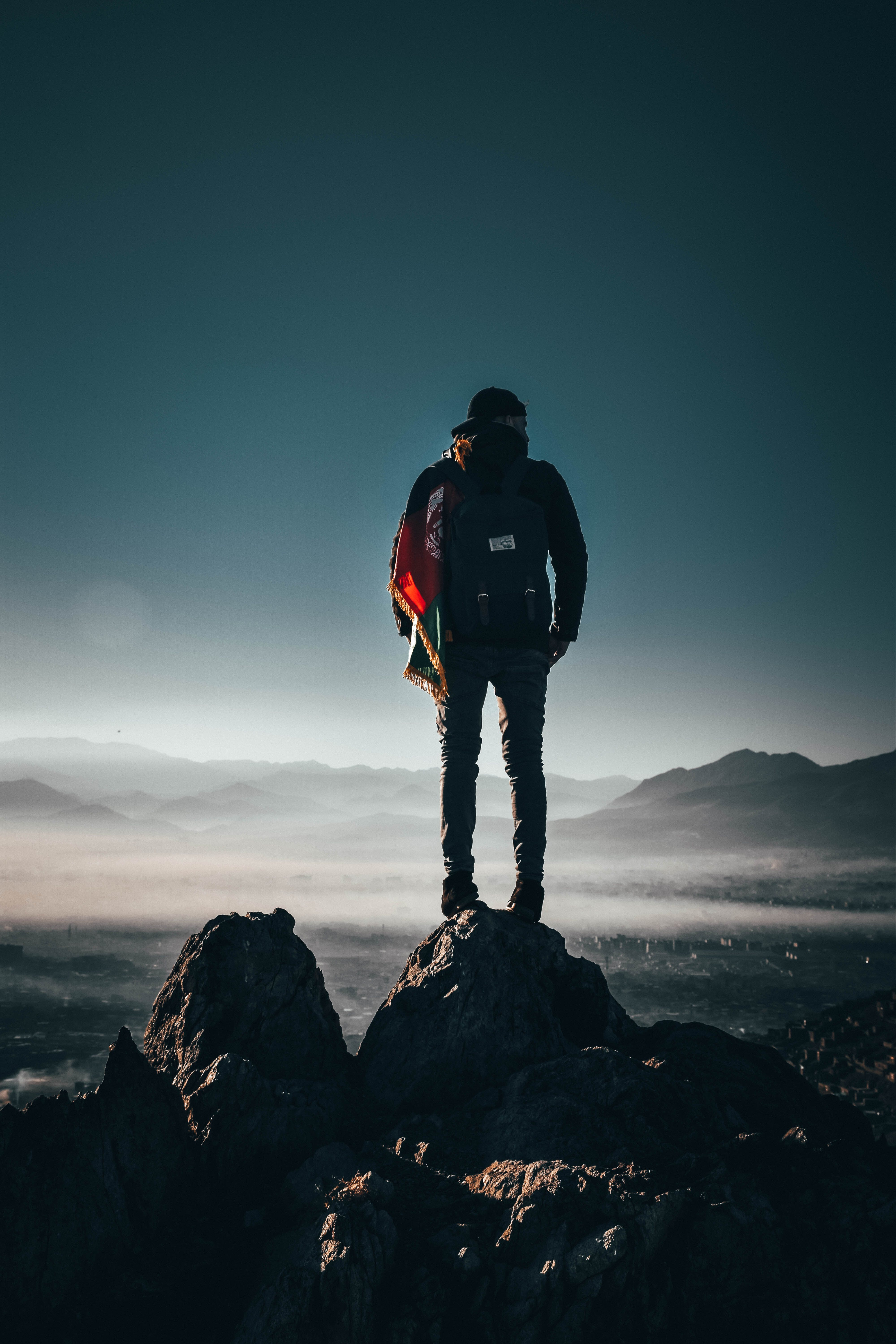 Man Carrying Backpack Standing on Rock Formation