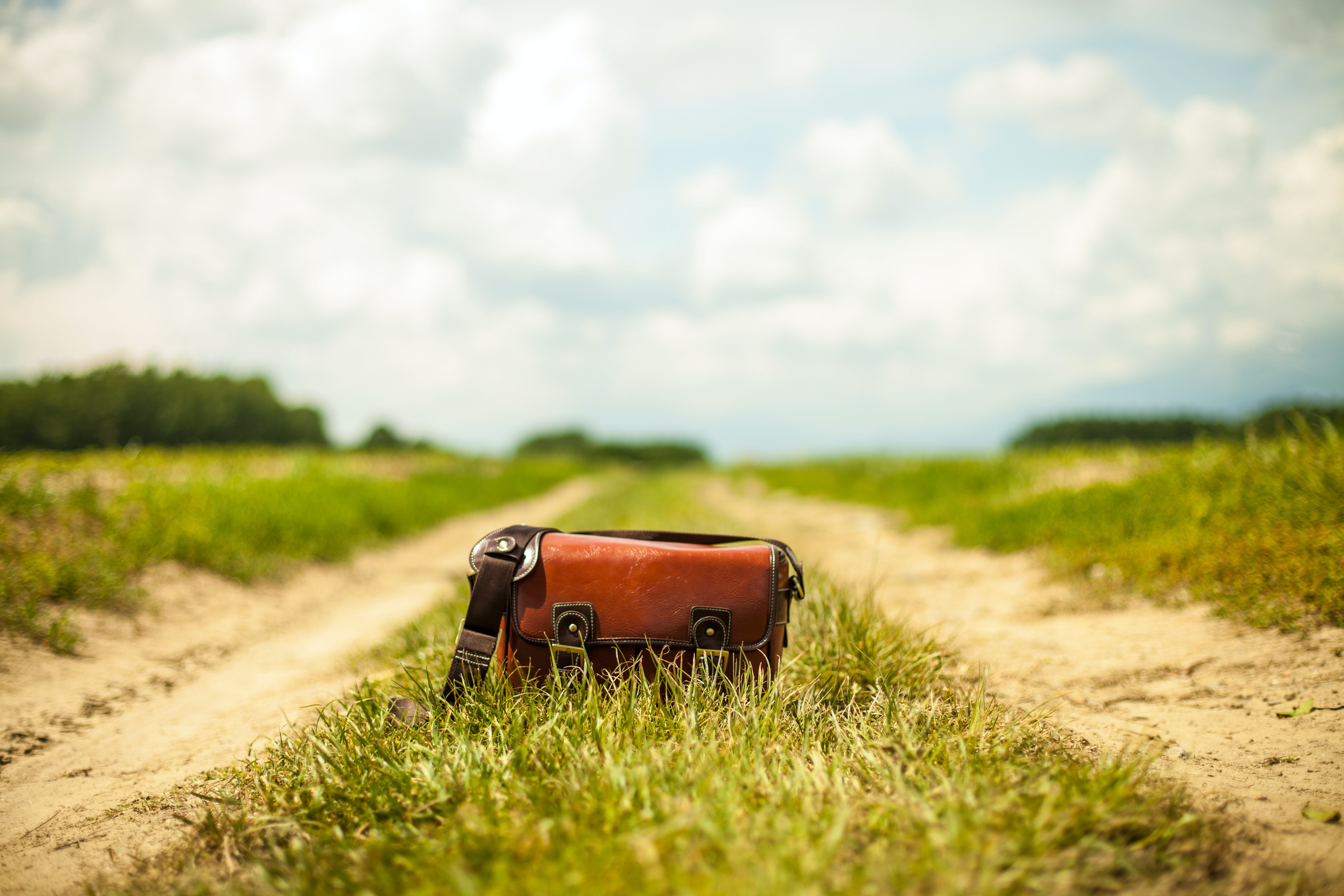 Brown Leather Baguette Bag on Green Grass Field With Vehicle Track