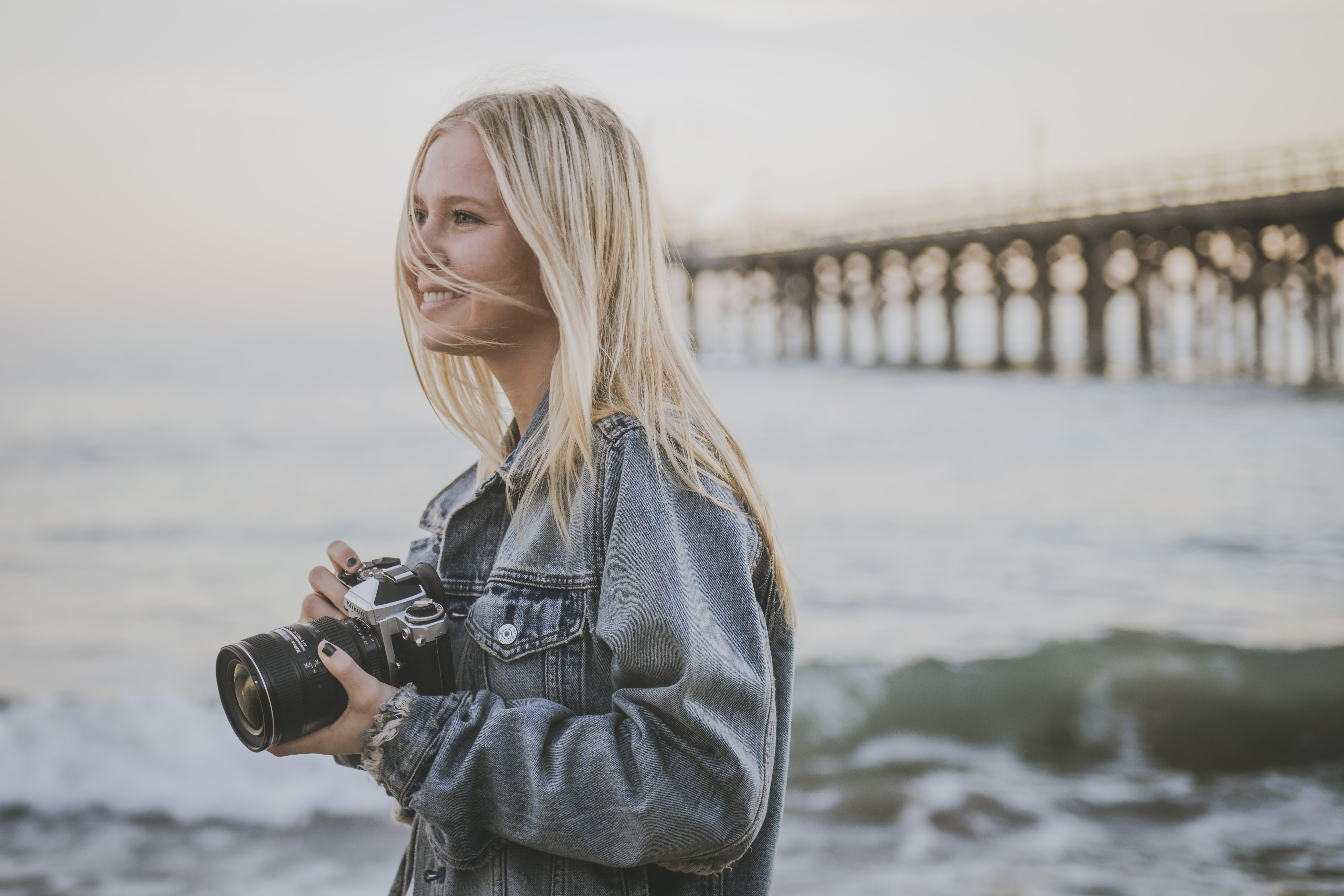Woman Taking Pictures Beside Ocean