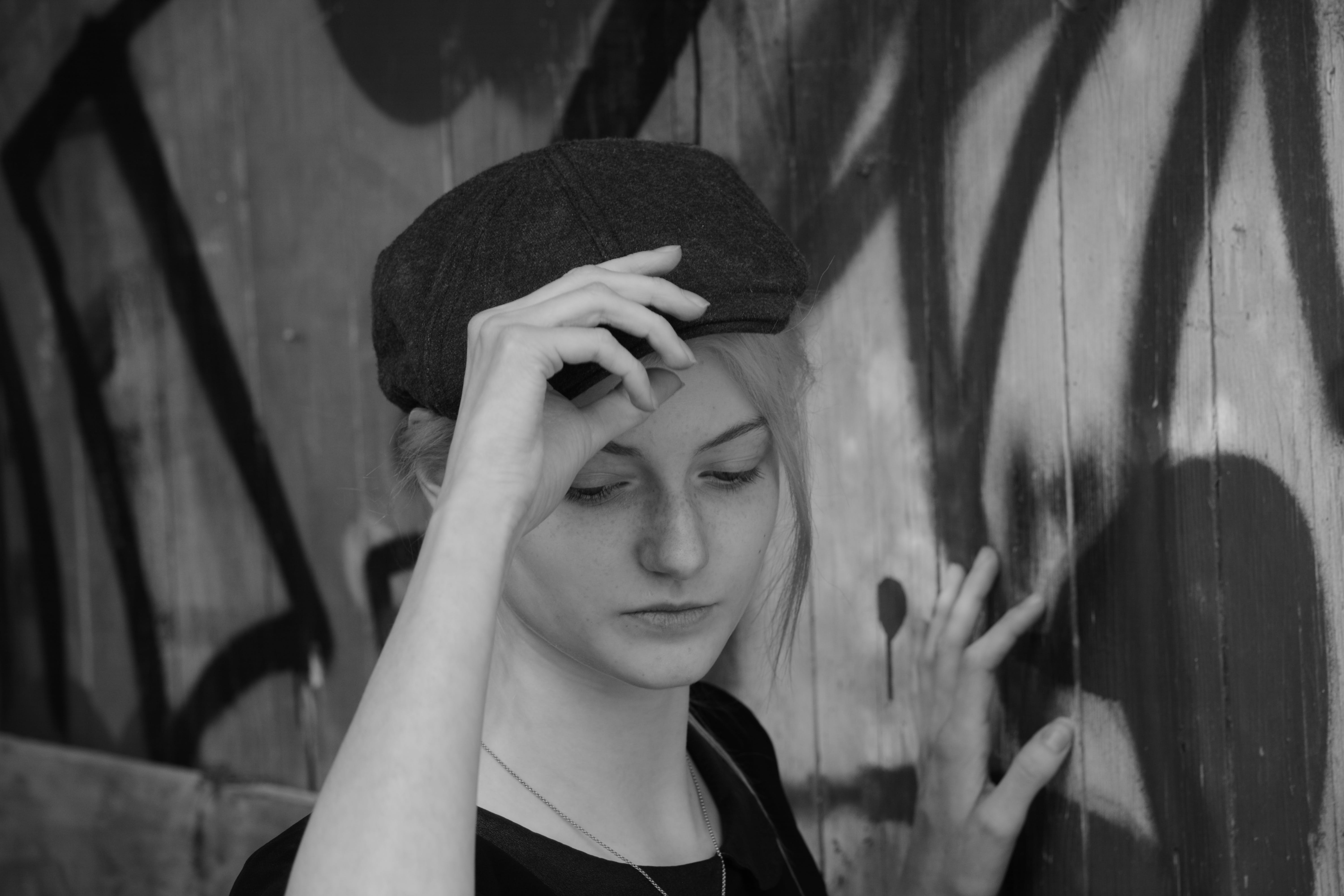 Woman Holding Her Cap in Grayscale