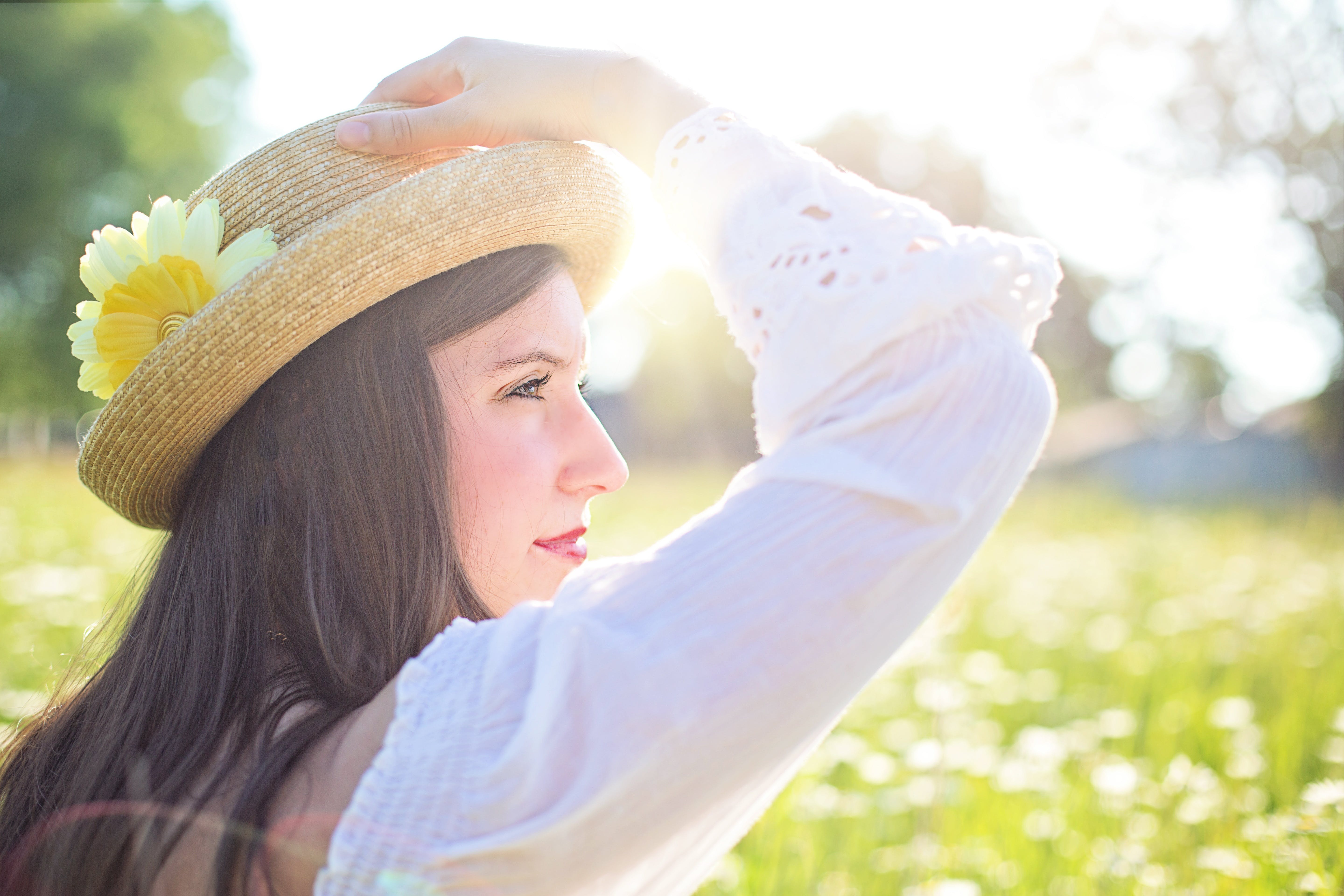 Woman in White Long Sleeve Shirt Wearing a Straw Hat during Daytime at Flower Field