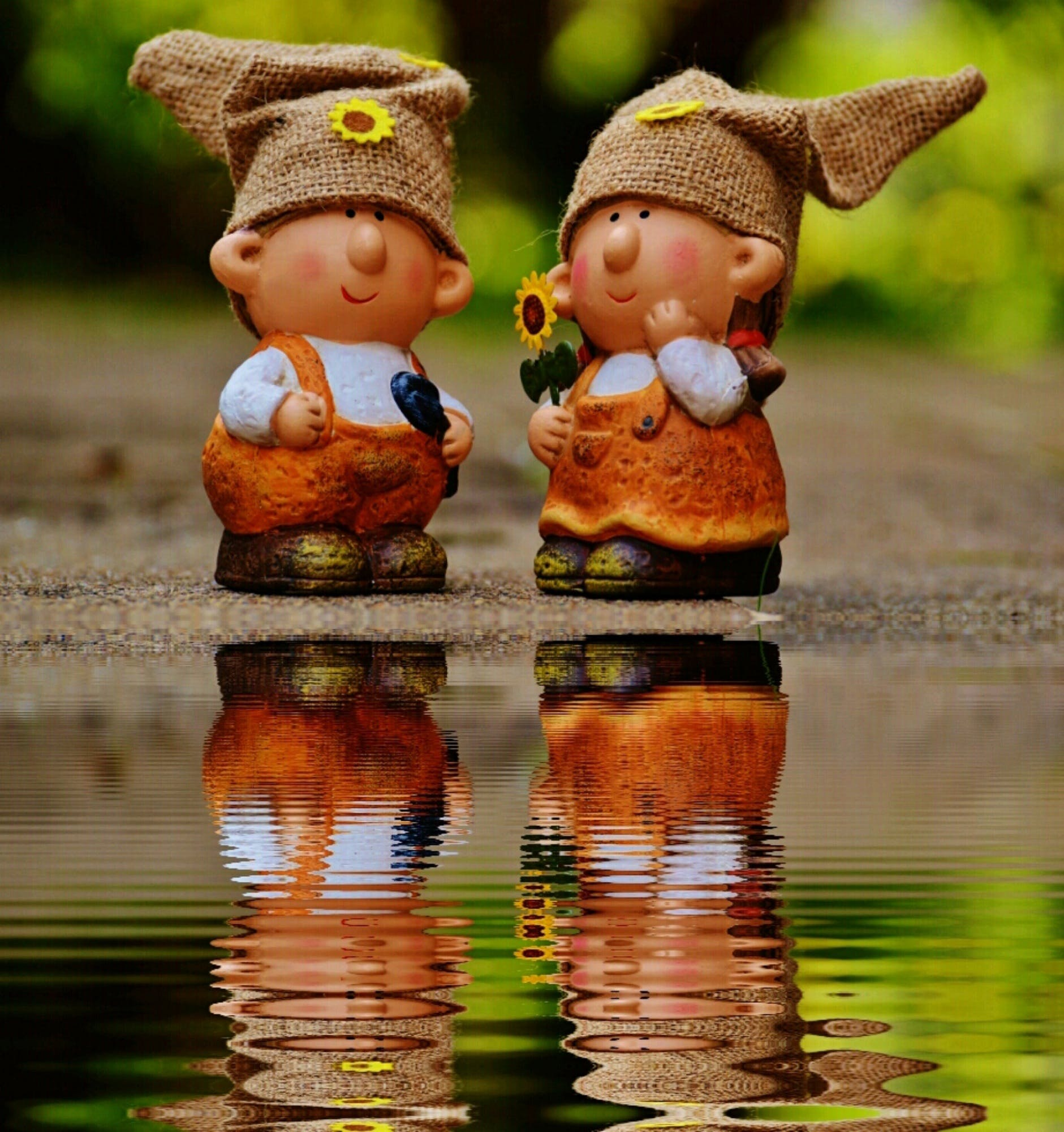 Girl and Boy Figurines Facing Each Other Near Body of Water