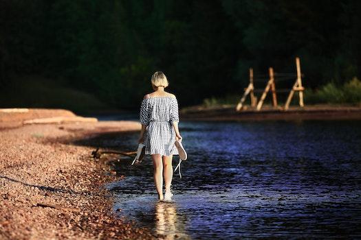 Woman Walking Near Body of Water