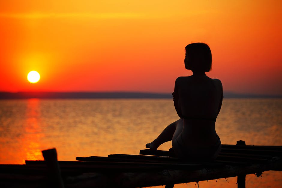 Silhouette of Woman Sitting on Dock during Sunset