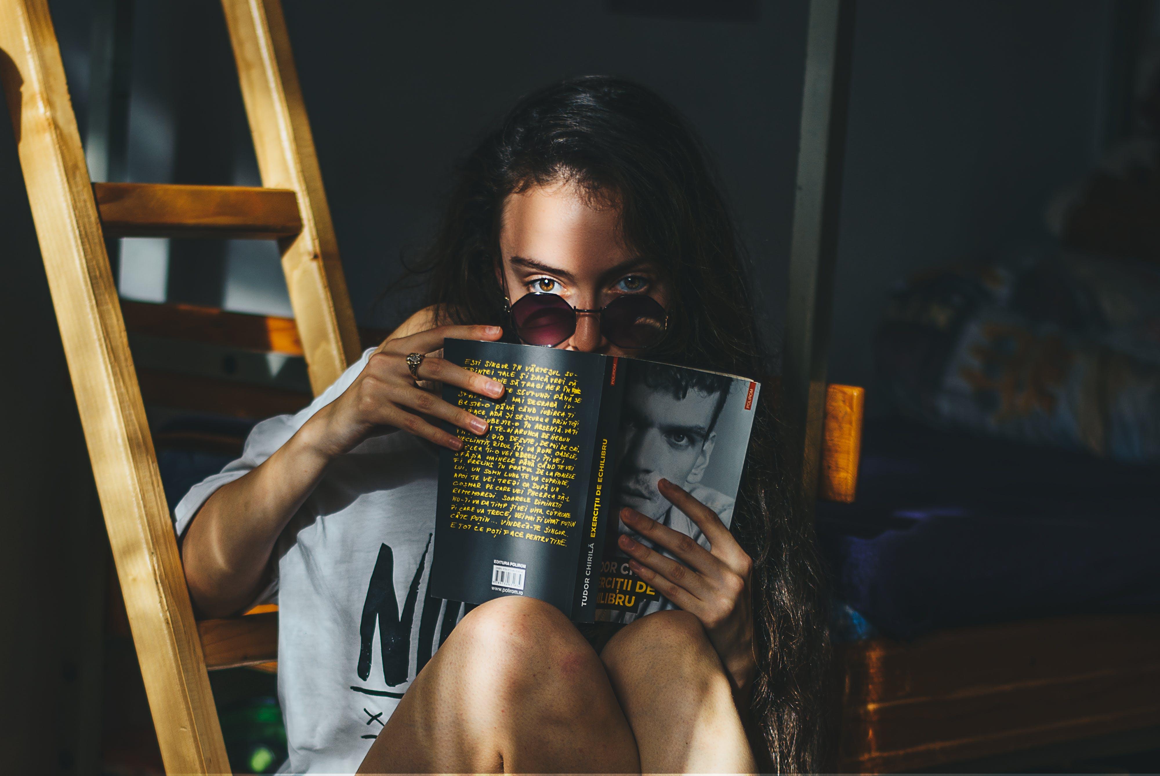 Woman Reading Magazine Beside Brown Wooden Ladder
