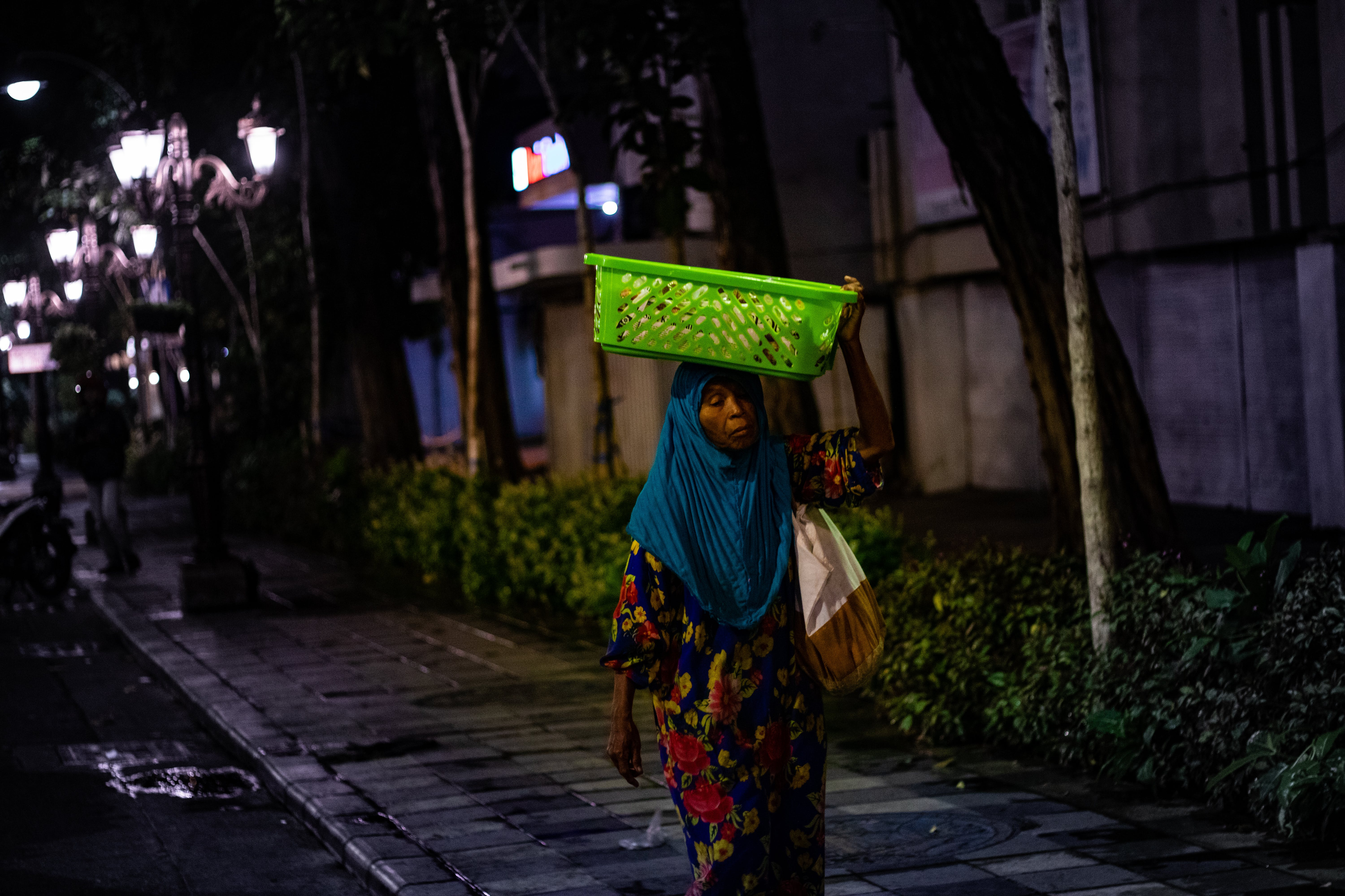 Woman Carrying Green Basket On Her Head