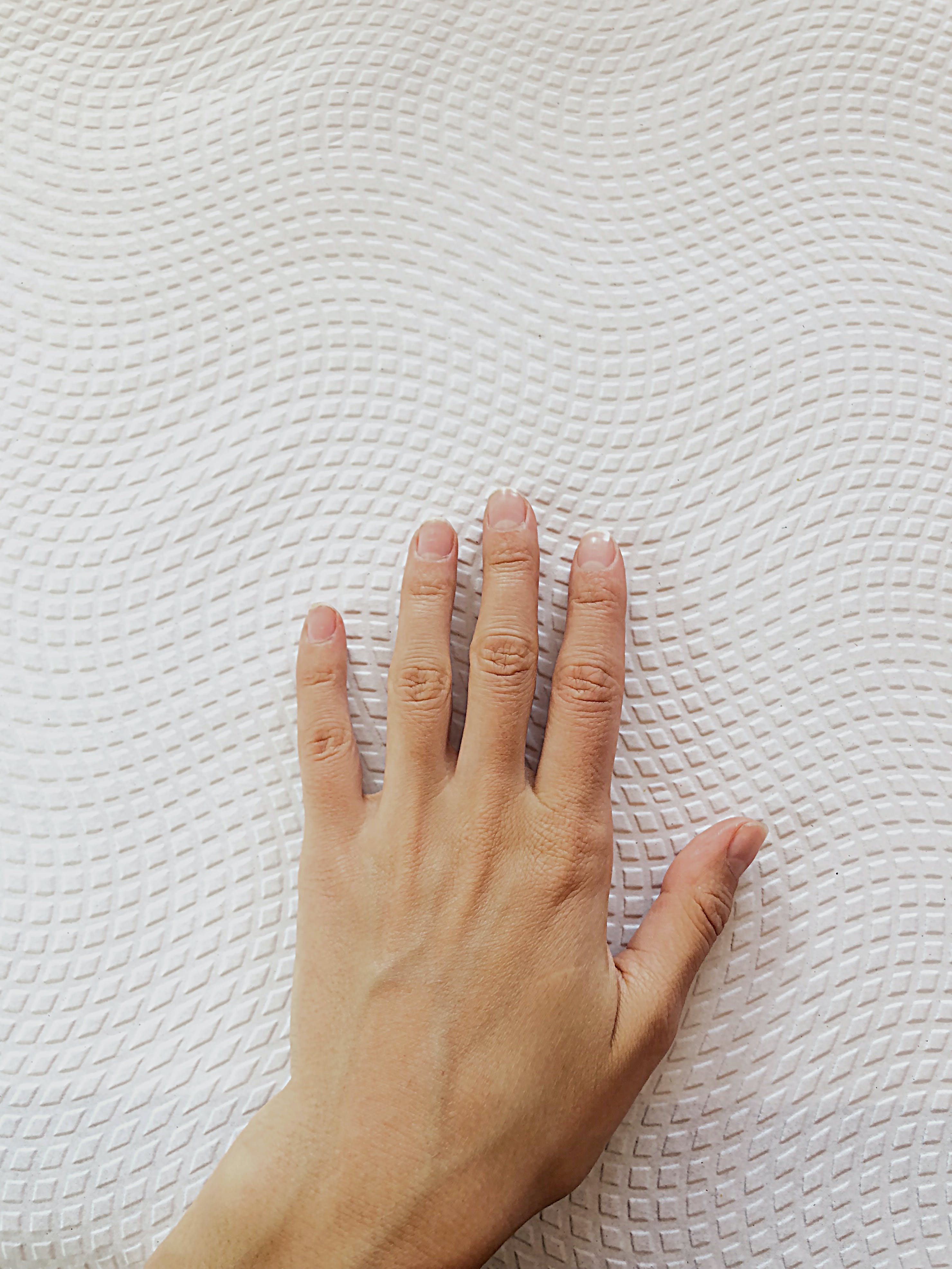 Left Human Hand on Quilted White Surface