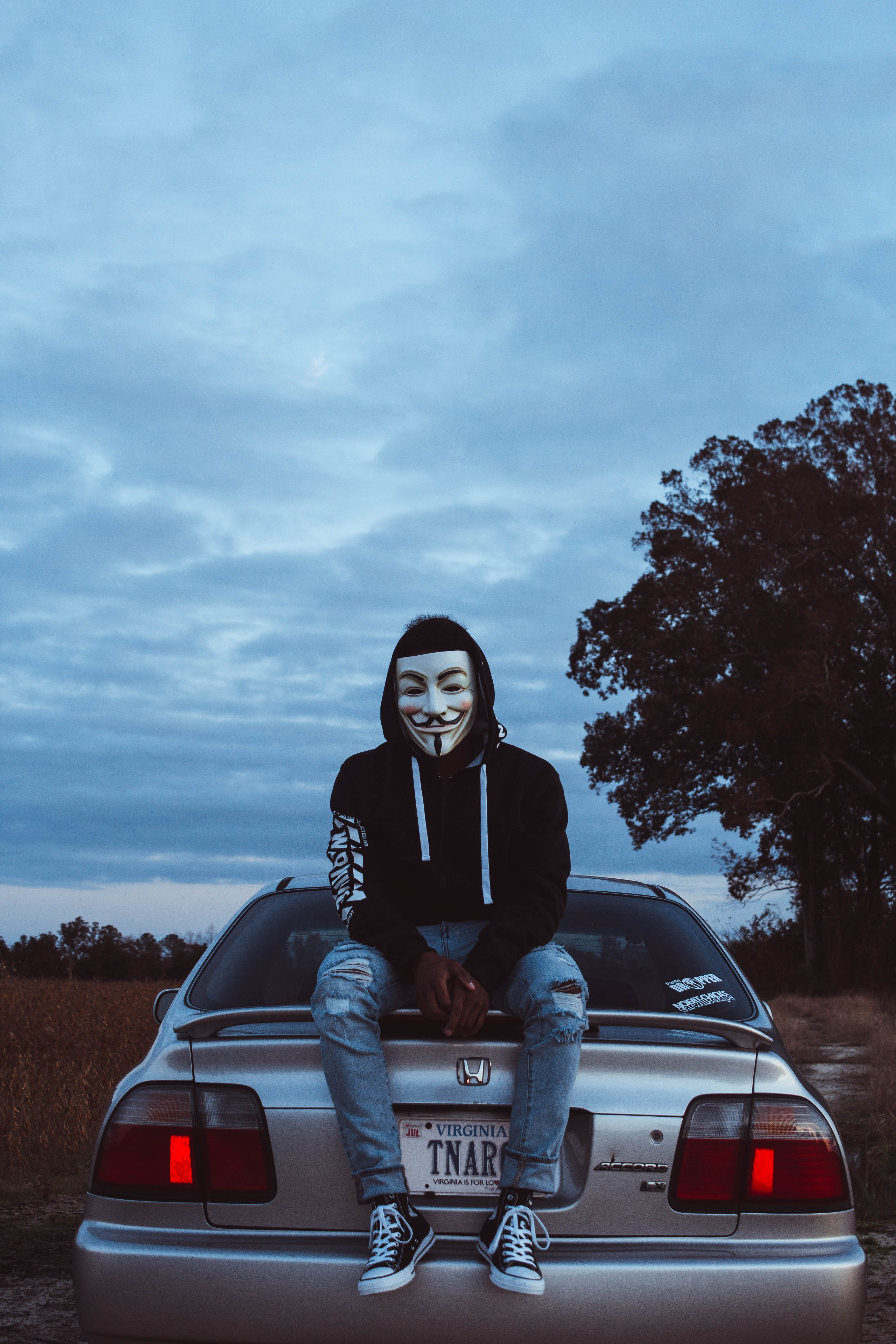 Man Wearing Guy Fawkes Mask While Sitting on Silver Honda Civic