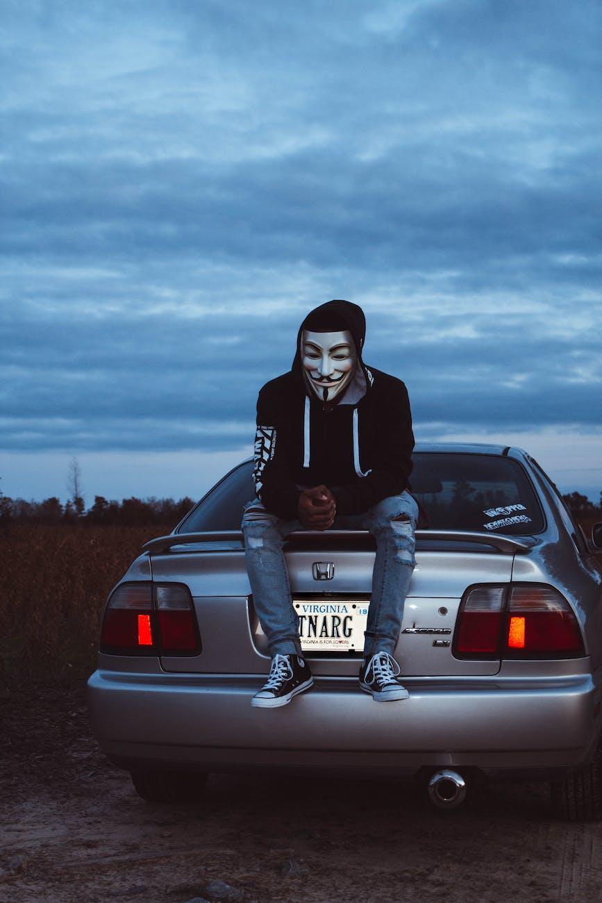 man wearing guy fawkes mask sitting on gray honda vehicle