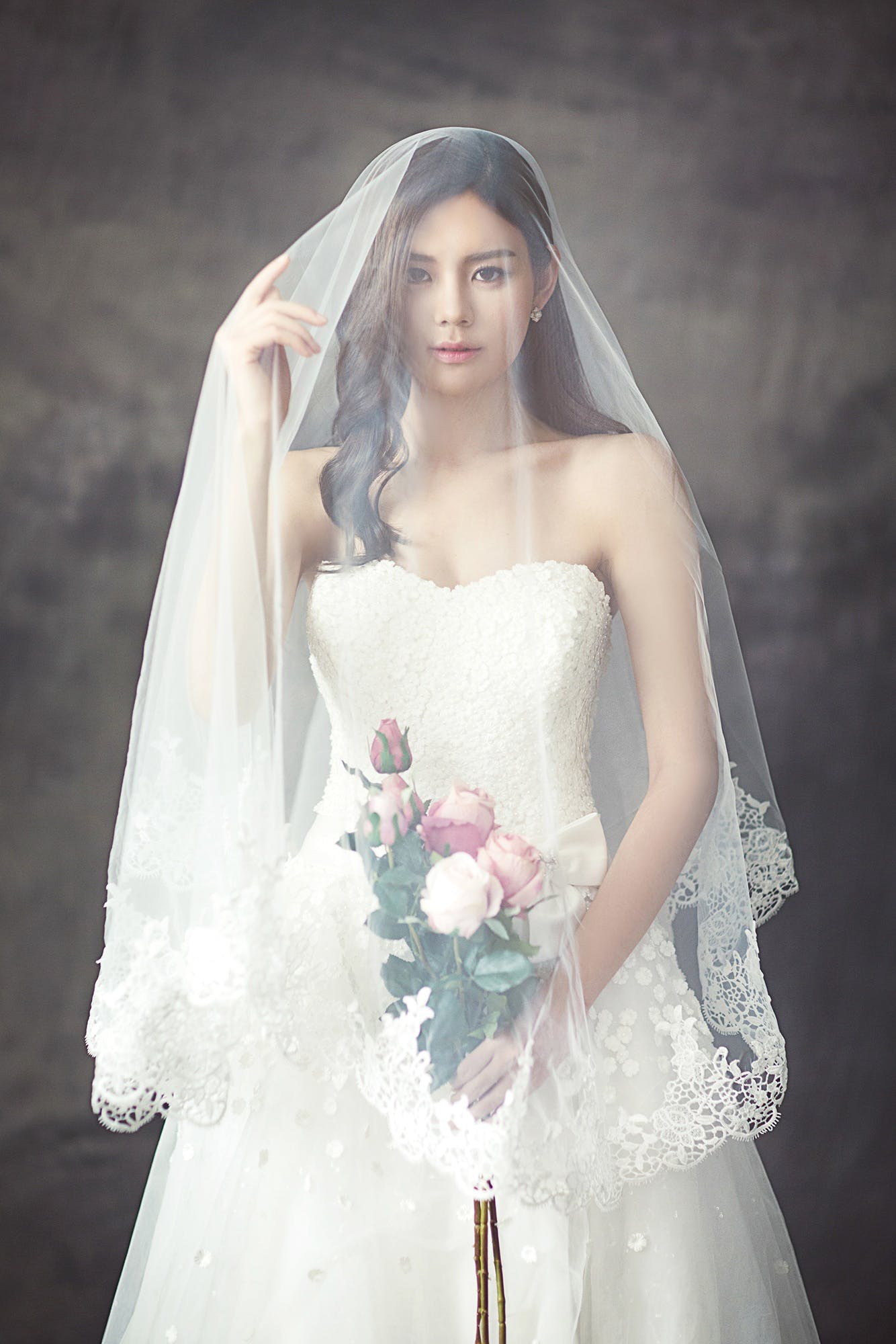 Woman in White Strapless Sweetheart Wedding Dress With Rose Bouquet Covered in White Veil