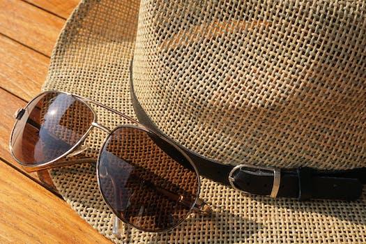 Brown Strawhat Beside Brown Aviator Sunglasses