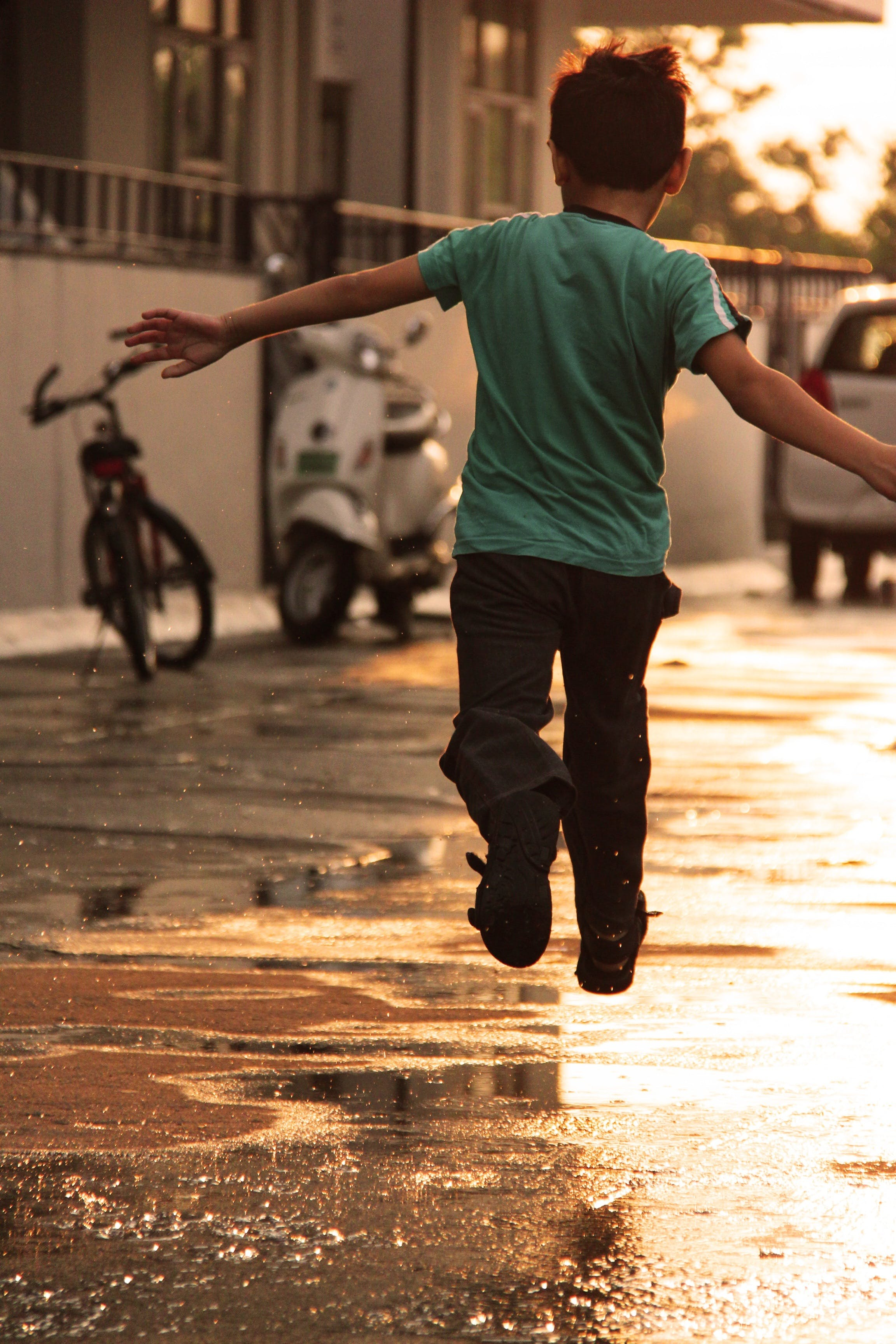 Boy in Green T Shirt Running on Wet Road during Daytime