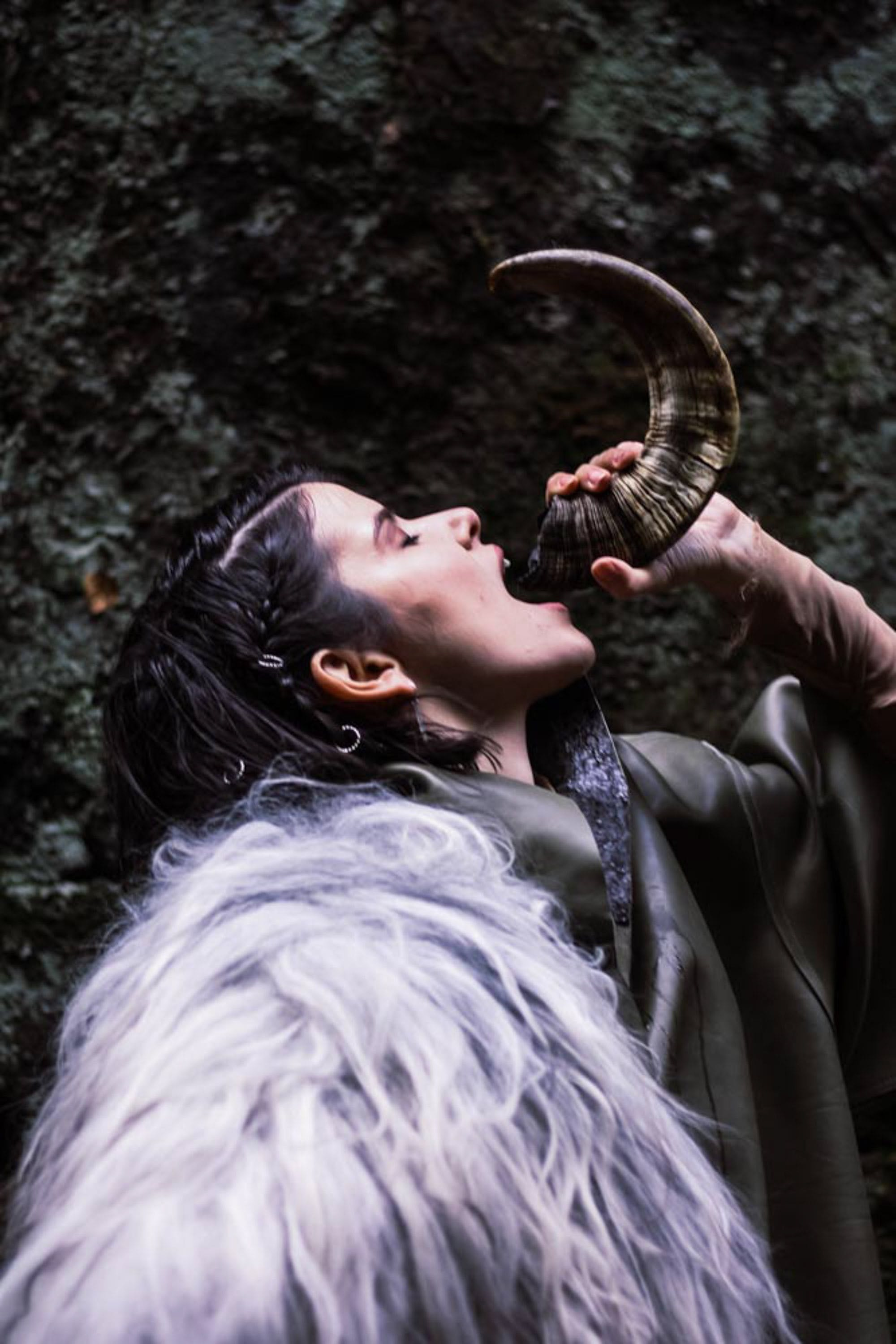 Woman Drinking Water On Animal Horn