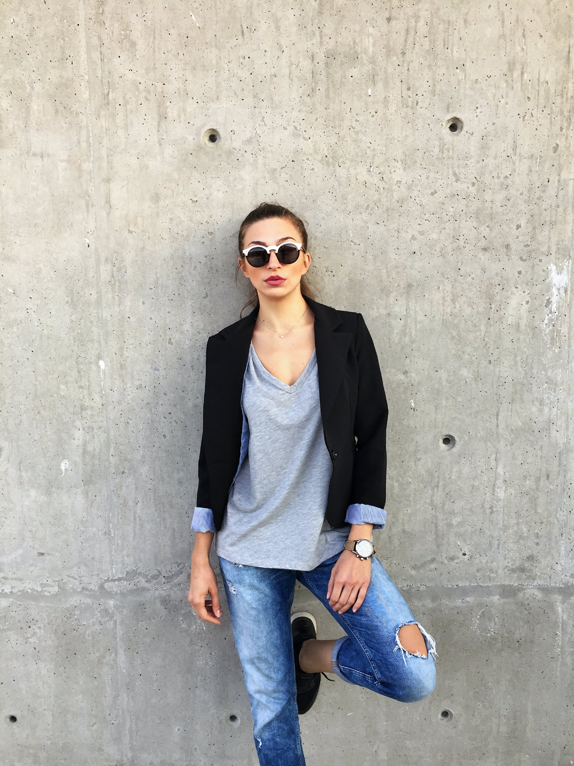 Woman Wearing Sunglasses Leaning on Concrete Wall With Left Toe on Wall