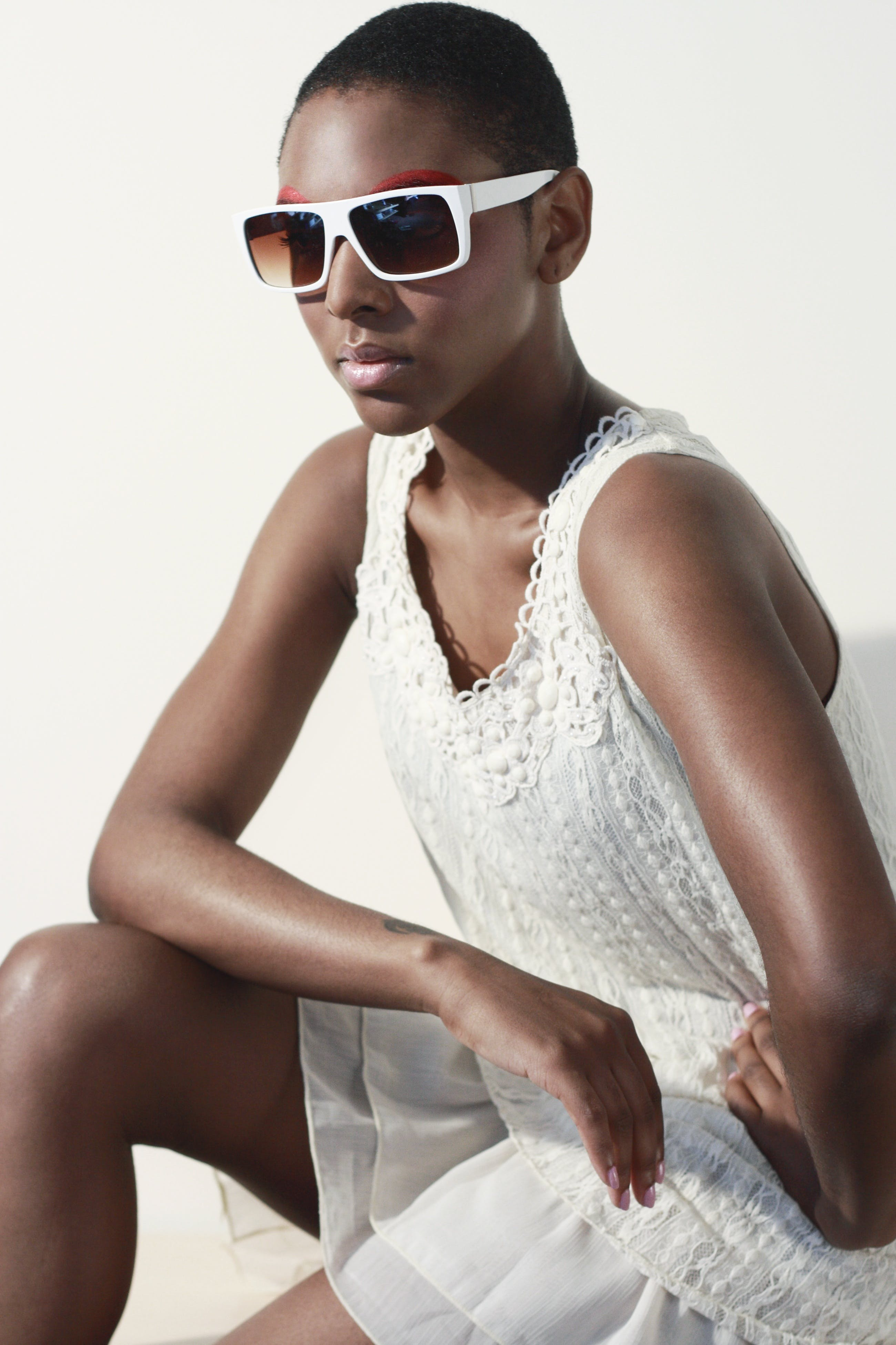Woman Wearing White Tank Dress and White Frame Sunglasses Sitting and Making a Pose