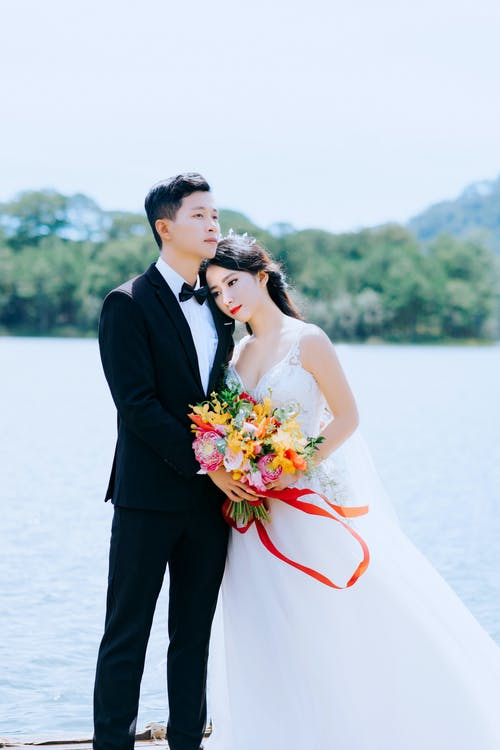 Photo of Couple Standing Near Body Of Water
