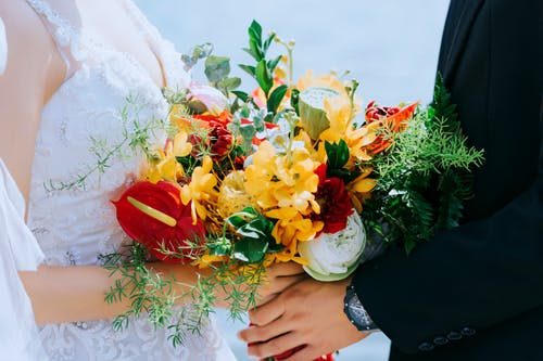 Bride and Groom Holding Bouquet of Flowers