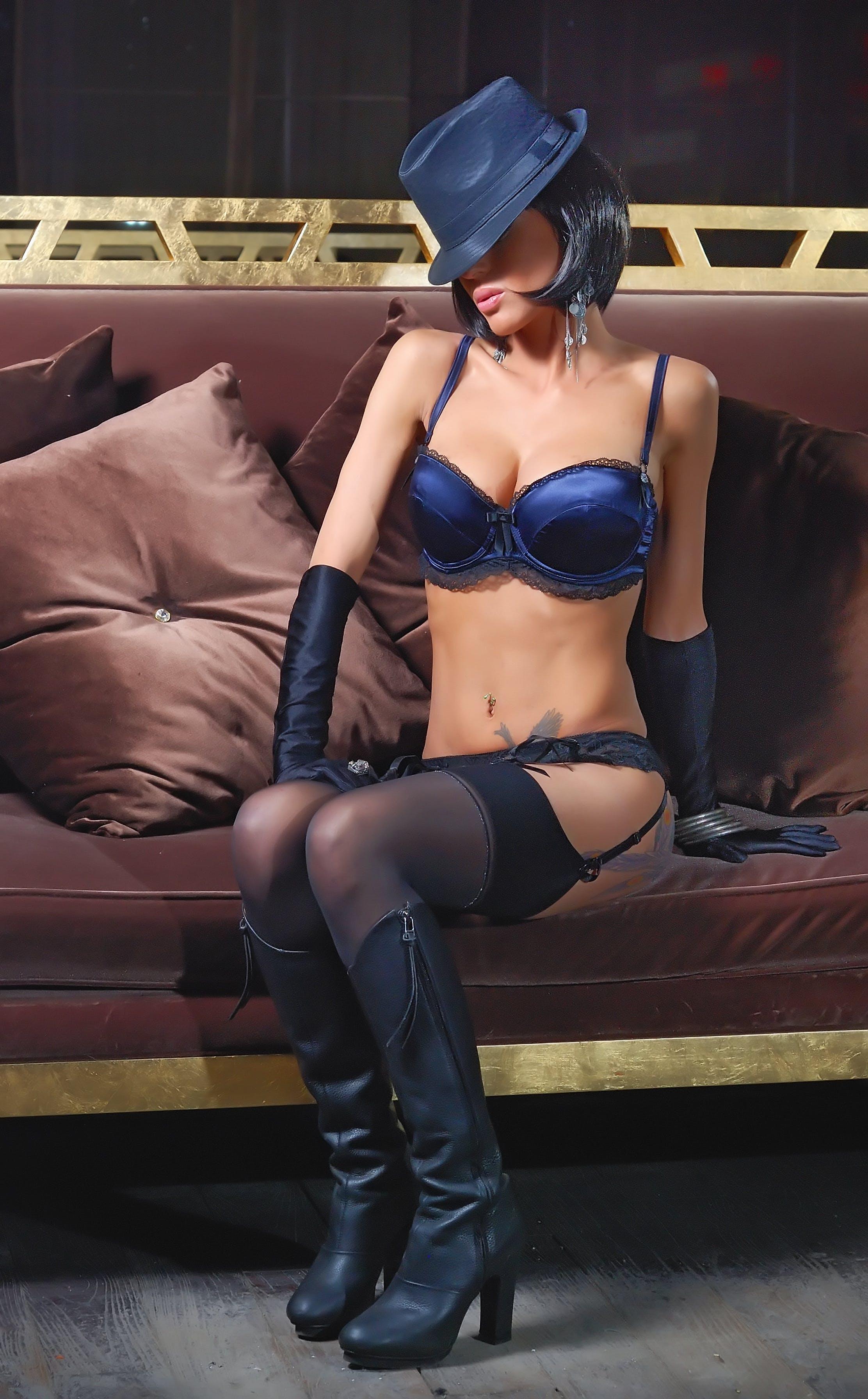 Woman in Blue Bikini Sitting Brown Sofa