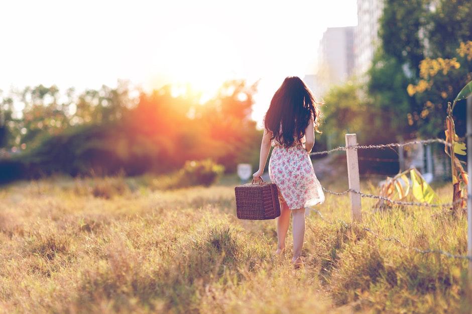 Woman in Brown Floral Dress Walking Near Fence