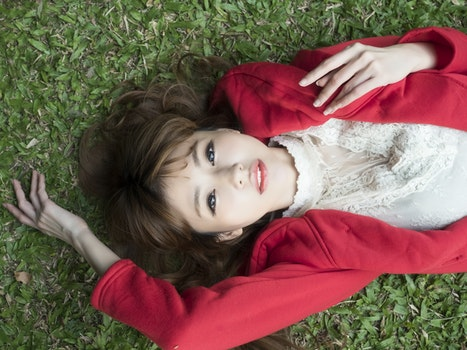 Woman in White Shirt Wearing Red Blazer Lying on Green Grass