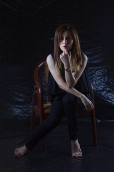 Woman Sitting on Brown Chair With Black Background