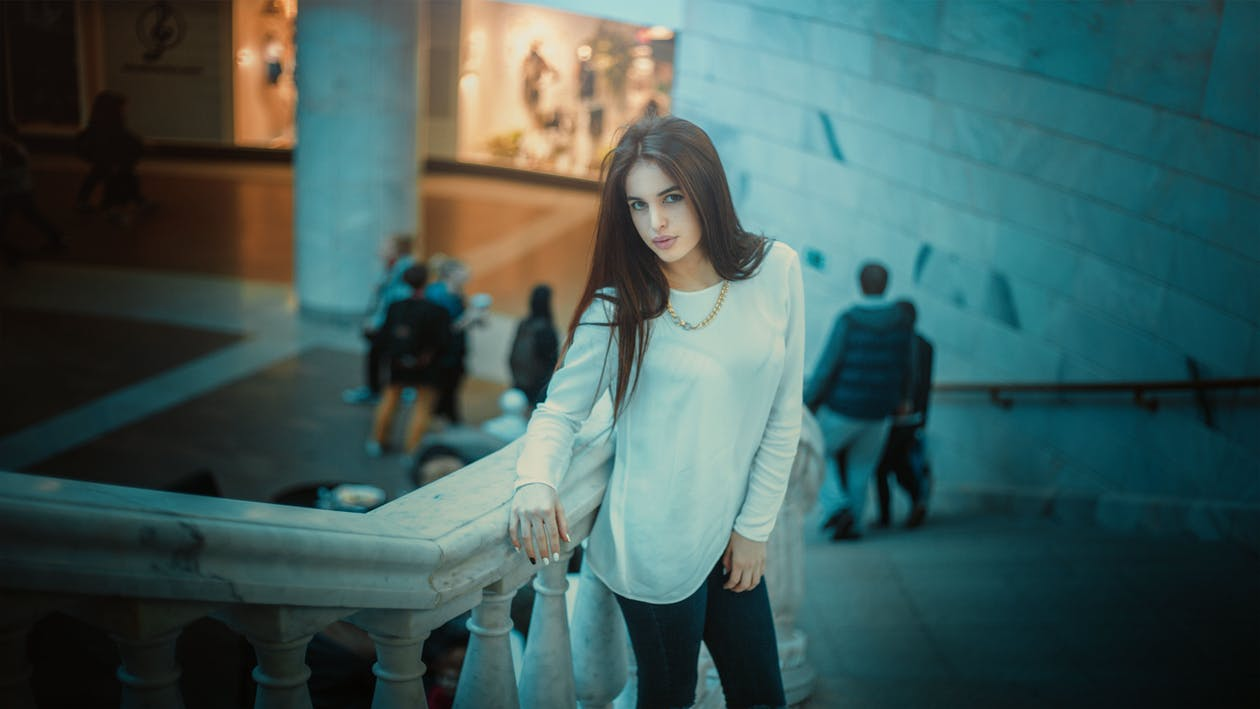 Woman in White Long Sleeve Shirt Posing Beside Gray Concrete Staircase