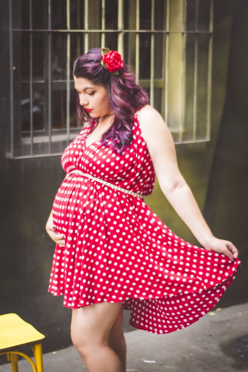Woman in Red and White Polka Dots Mini Dress Holding Her Stomach