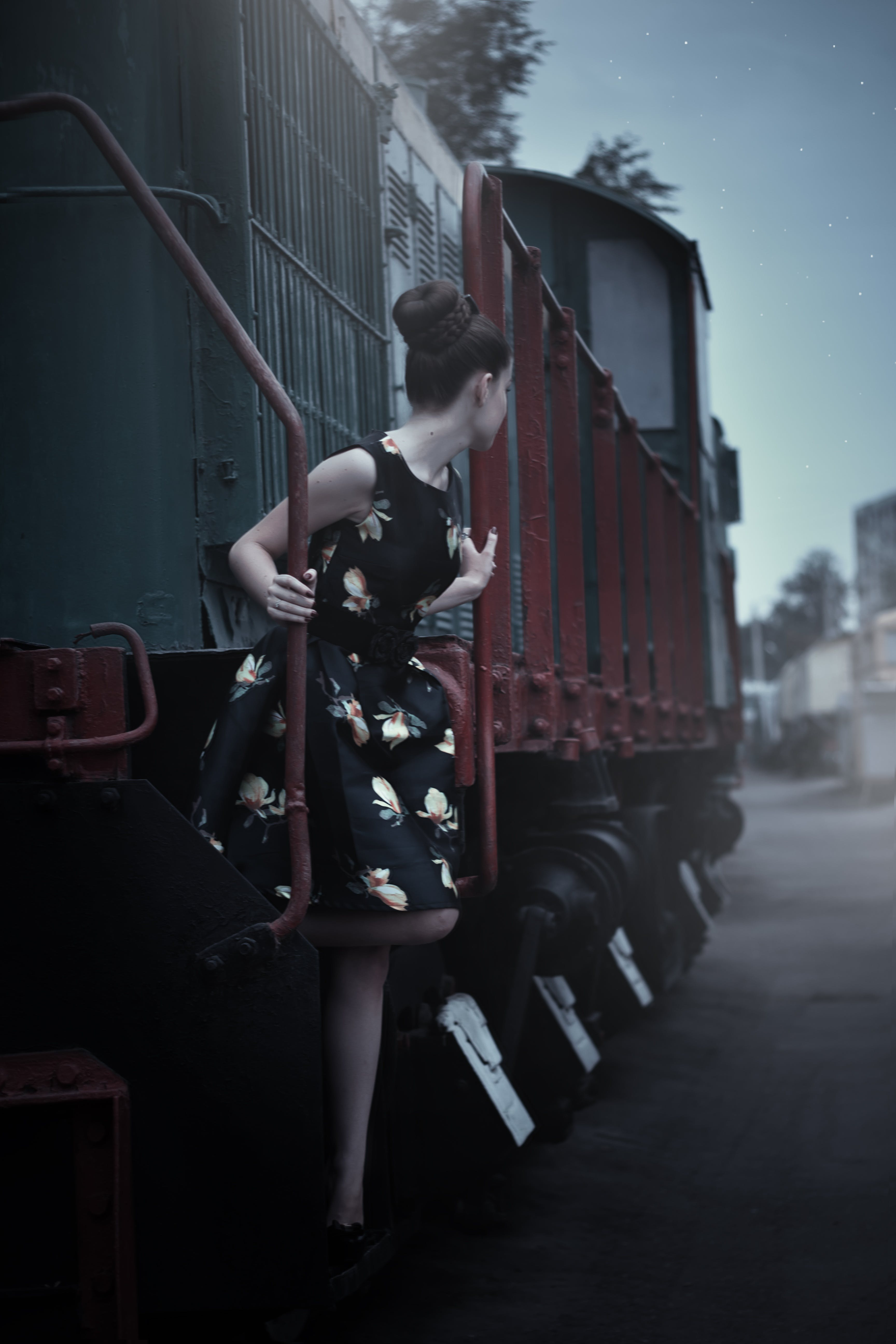 Woman in Black Sleeveless Dress Standing Beside Train