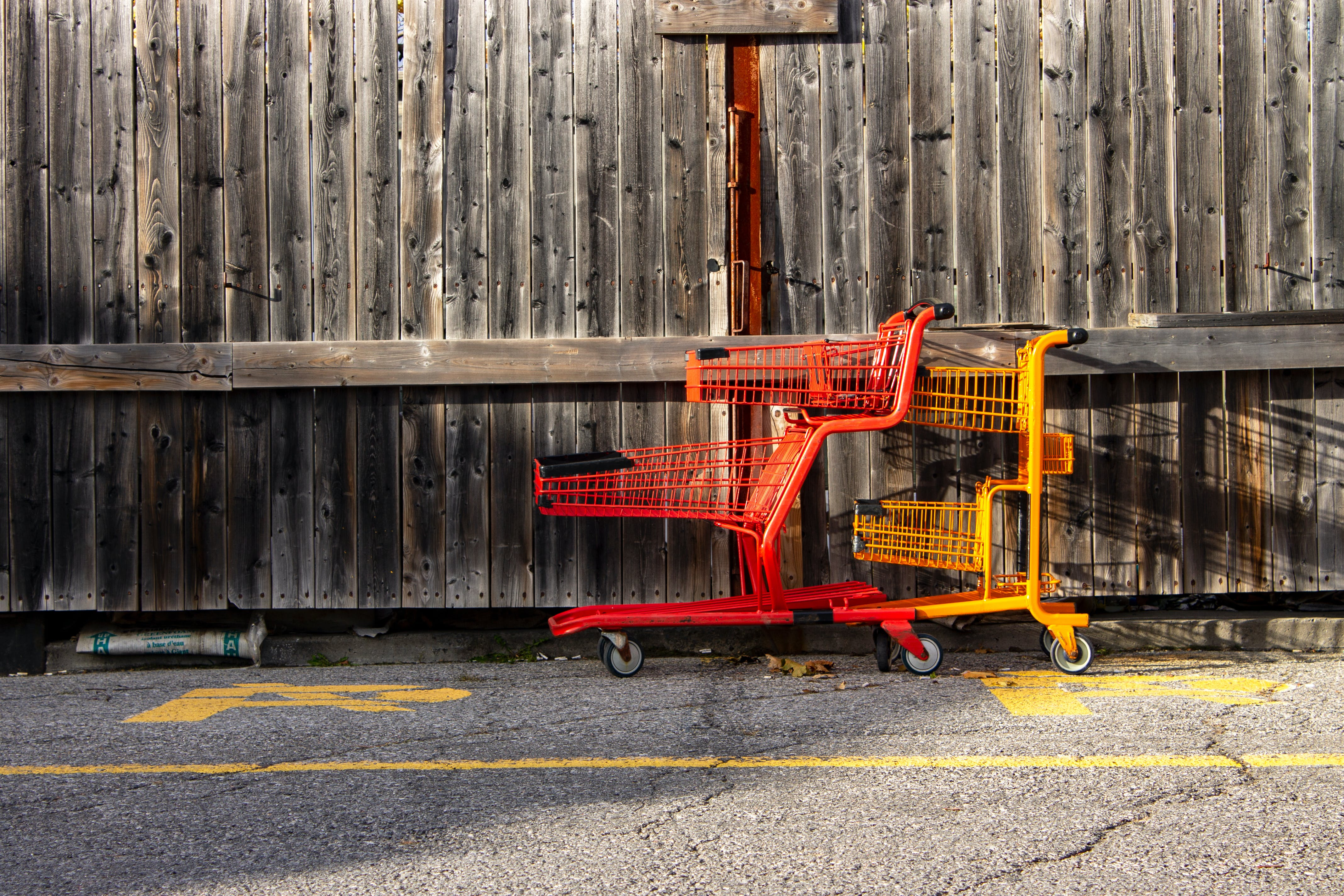 Two Red and Yellow Shopping Carts Beside Wall