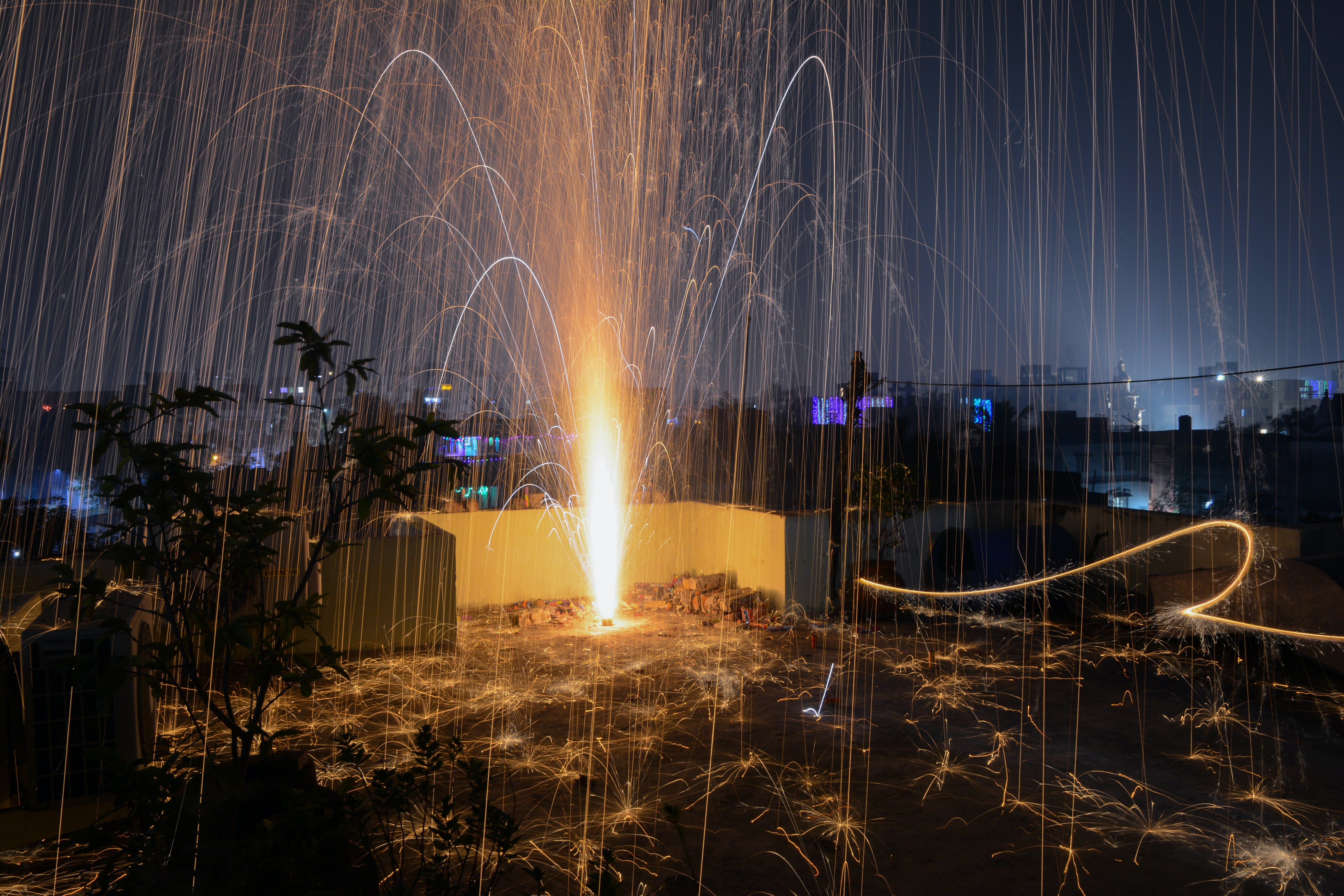 Steel Wool Photography of Plant on Roof Top during Nighttime
