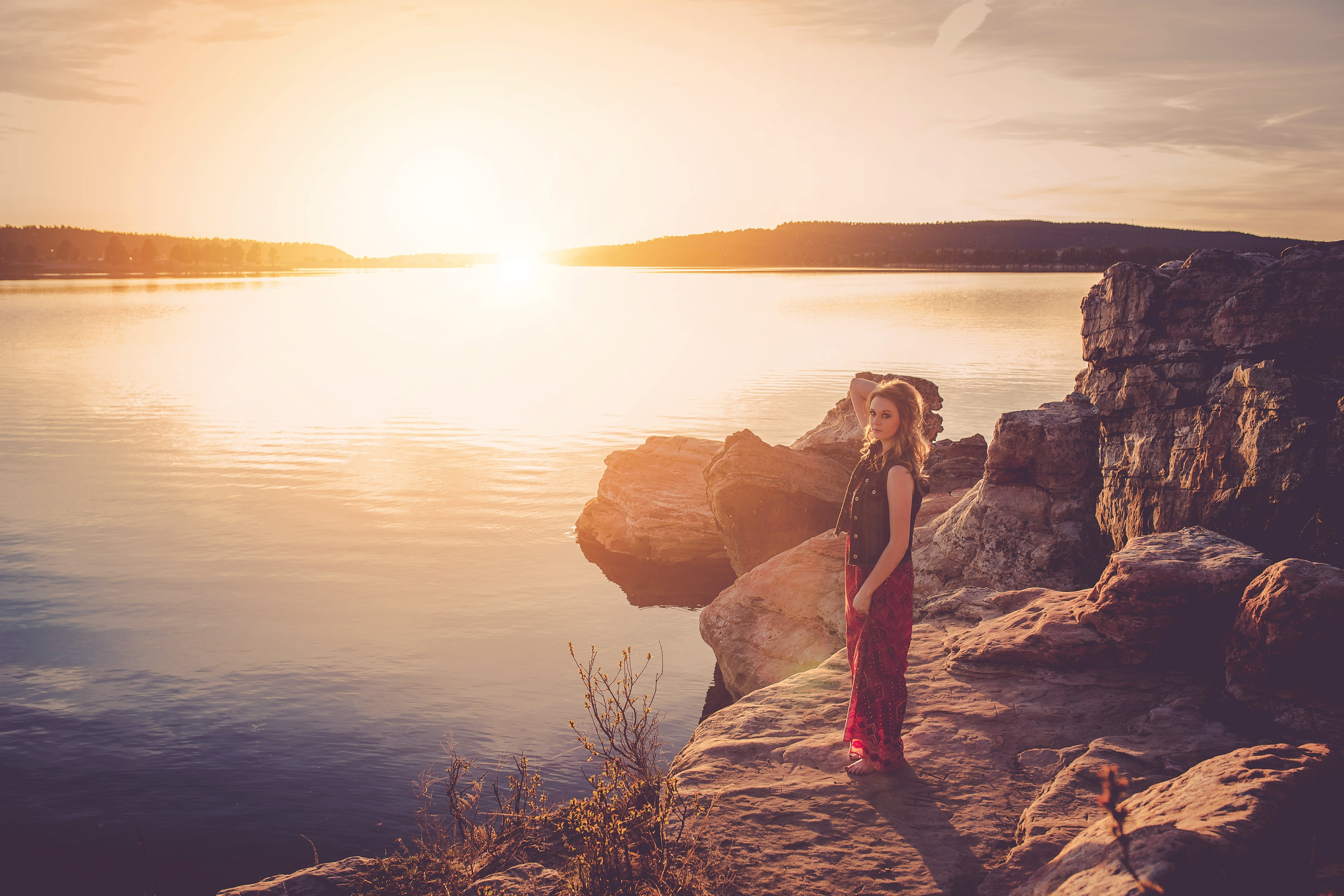 Woman in Black and Red Sleeveless Dress Standing Near Large Body of Water during Sunset