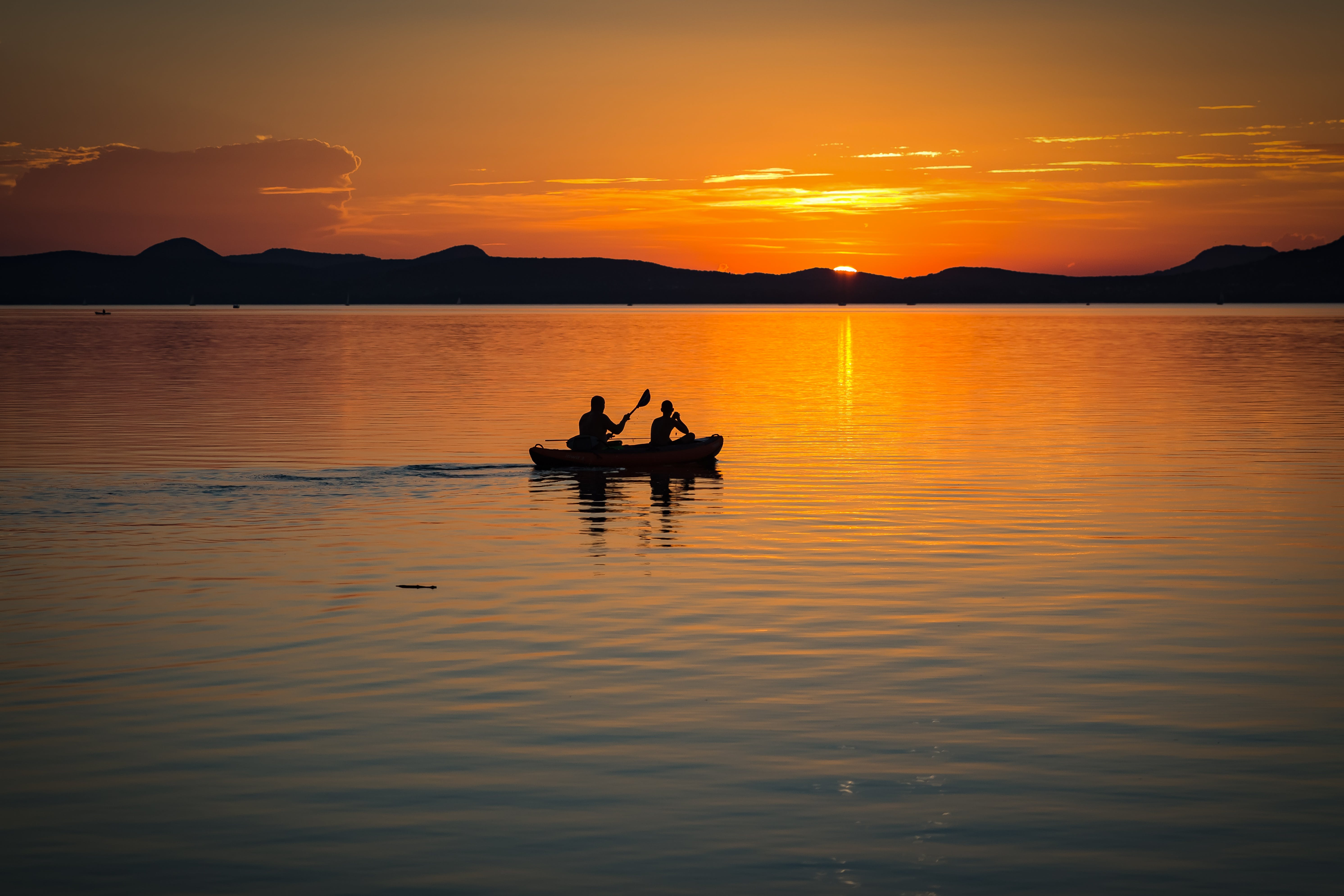2 Person on Boat Sailing in Clear Water during Sunset