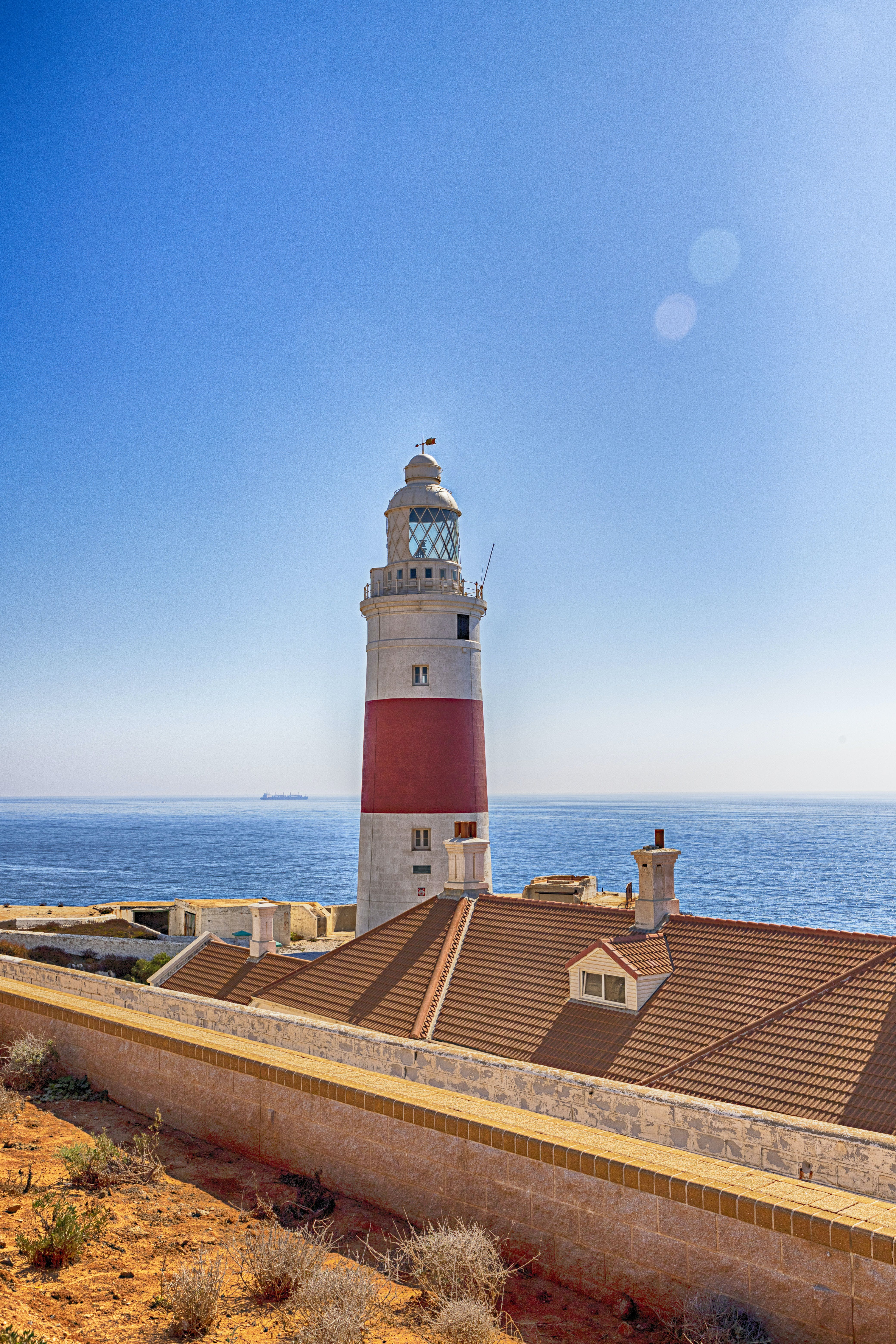 White and Red Lighthouse Beside Sea Landscape Photography