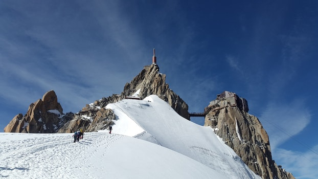 People Walking Toward Top of Mountain on Snow Covered Ground during Daytime