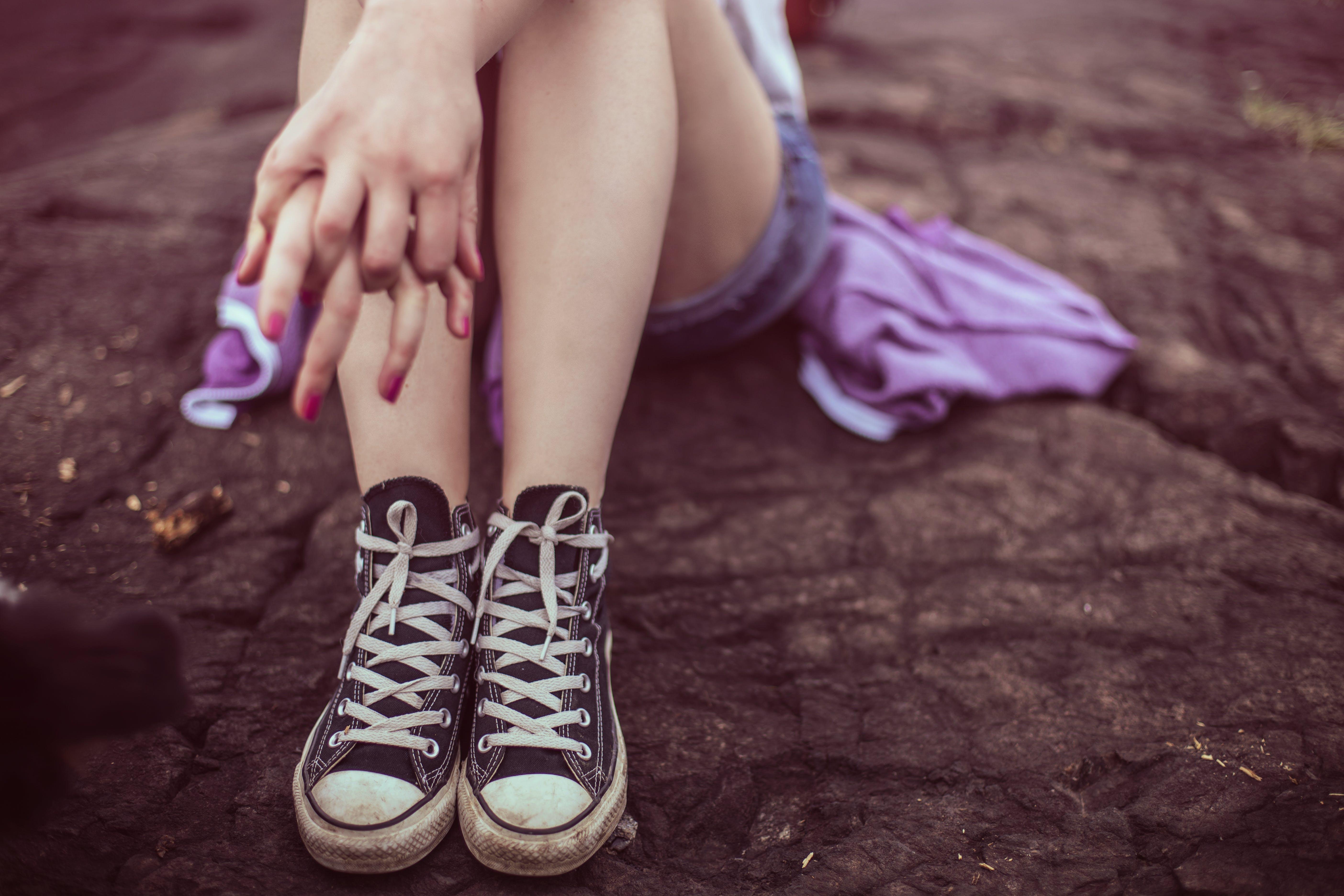 Woman Wearing Pair of Black Sneakers