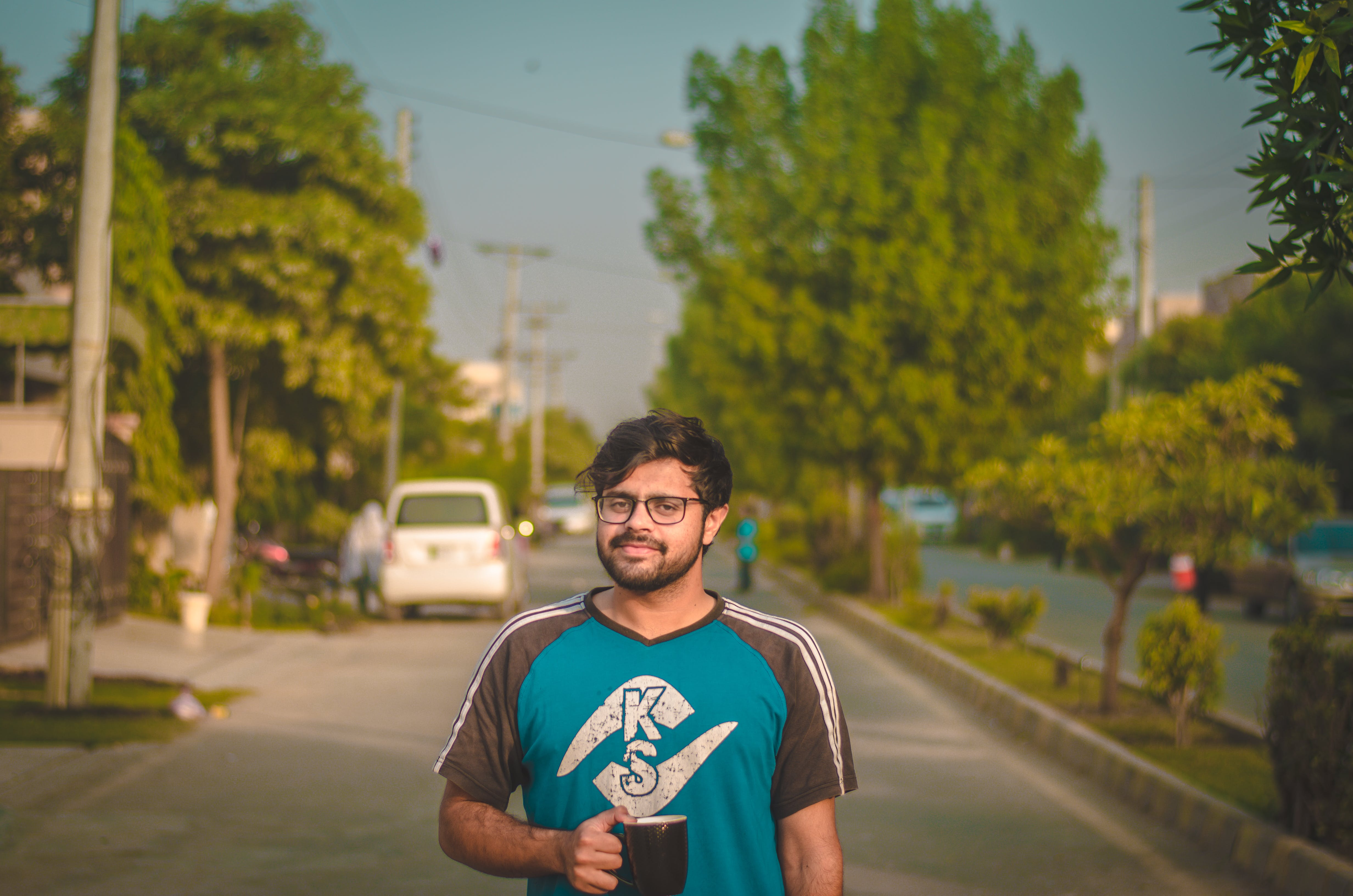 Man Standing on Road While Holding Black Ceramic Mug