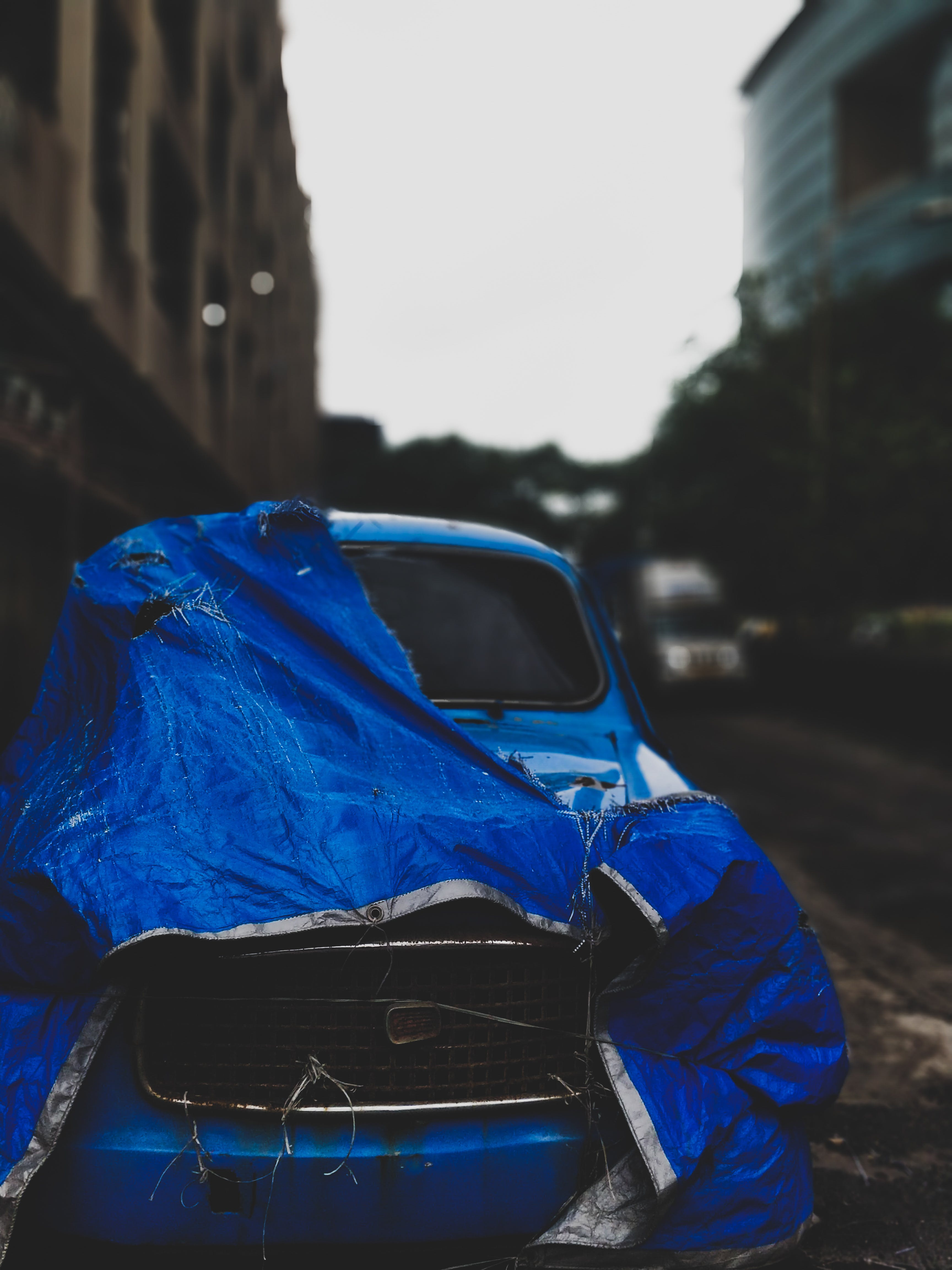 Abandoned Classic Blue Car With Blue Tarp Parked Beside Concrete Building