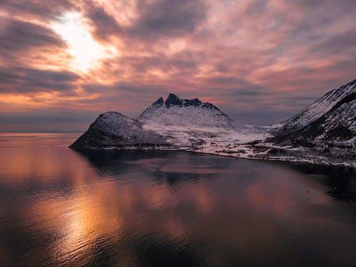 Mountain Beside Ocean During Golden Hour